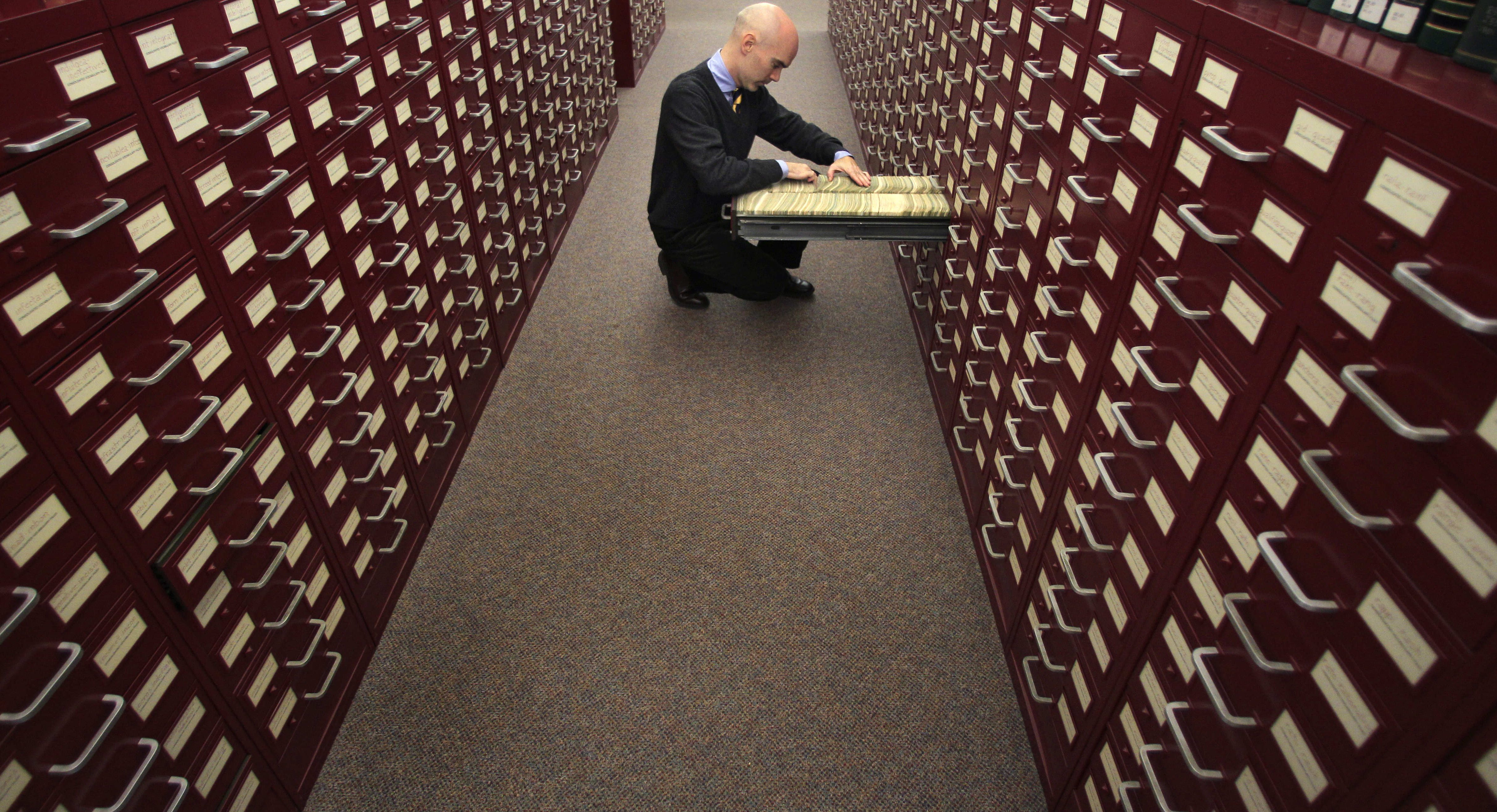 """In this Tuesday, Dec. 14, 2010 photo, Peter Sokolowski, editor at large for Merriam-Webster Inc., thumbs through the index card files at the dictionary publisher, in Springfield, Mass. Merriam-Webster has chosen """"austerity"""" as its 2010 Word of the Year. (AP Photo/Charles Krupa)"""