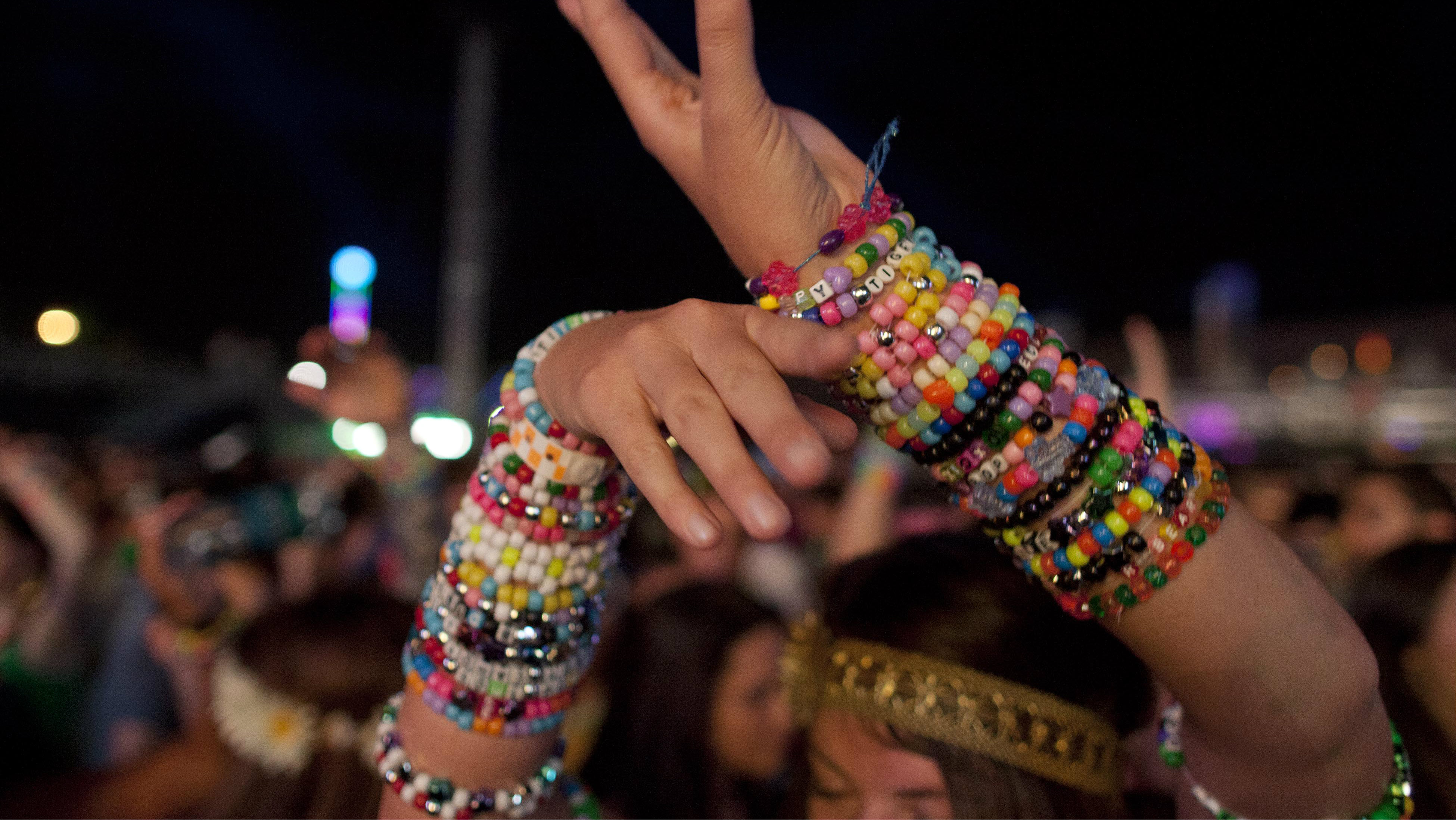"A rave goer dances with her rave ""candy"" bracelets."
