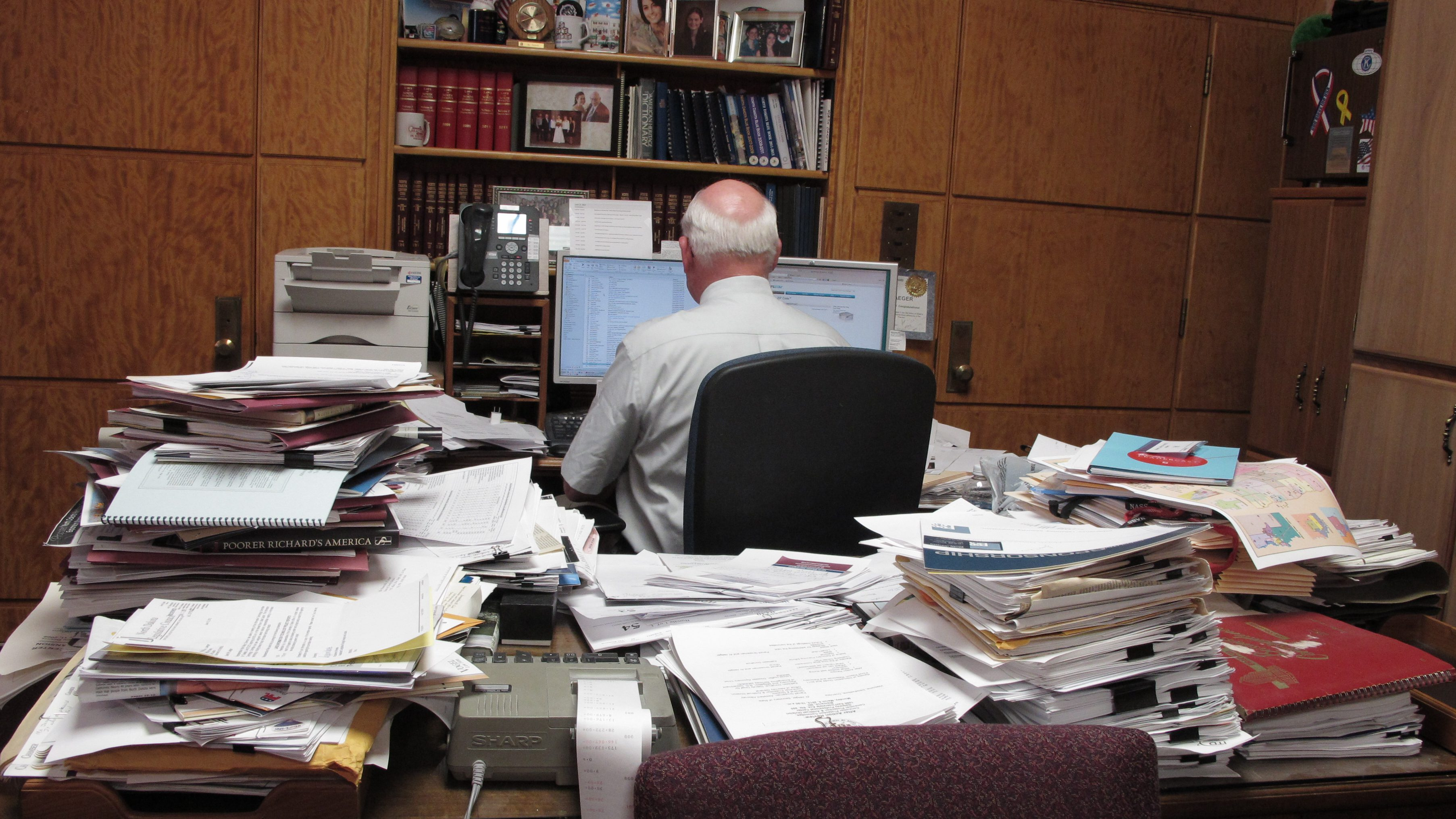 In this Wednesday, June 13, 2012 photo, North Dakota Secretary of State Al Jaeger works at a computer keyboard opposite his desk, which is stacked high with papers. Jaeger received permission Tuesday, June 19, 2012 from a legislative committee to hire three new employees to help his office get caught up on business registration paperwork. Registration processing is done elsewhere in the secretary of state's office in the North Dakota Capitol in Bismarck, N.D. (AP Photo/Dale Wetzel)