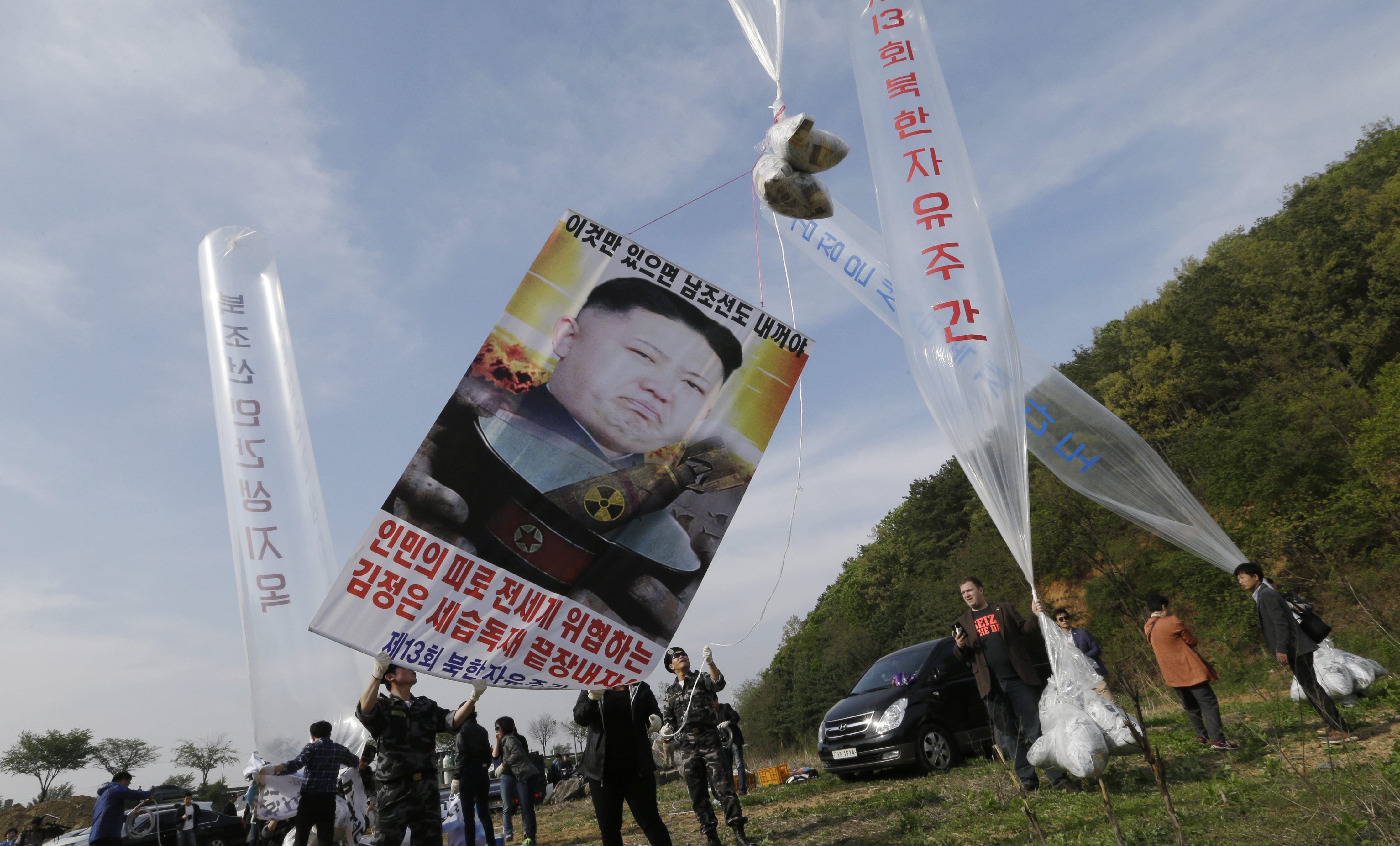 "North Korean defectors prepare to release balloons carrying leaflets and a banner condemning North Korean leader Kim Jong Un during a rally against North Korea in Paju, near the border with North Korea, South Korea, Friday, April 29, 2016. North Korea on Friday accused U.S. soldiers of trying to provoke its frontline troops with ""disgusting"" acts and encouraging South Korean soldiers to aim their guns at the North. The banner reads "" End the three generation dictatorship."""