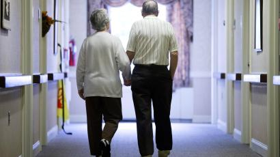 Elderly couple walking down the hall of an apartment building