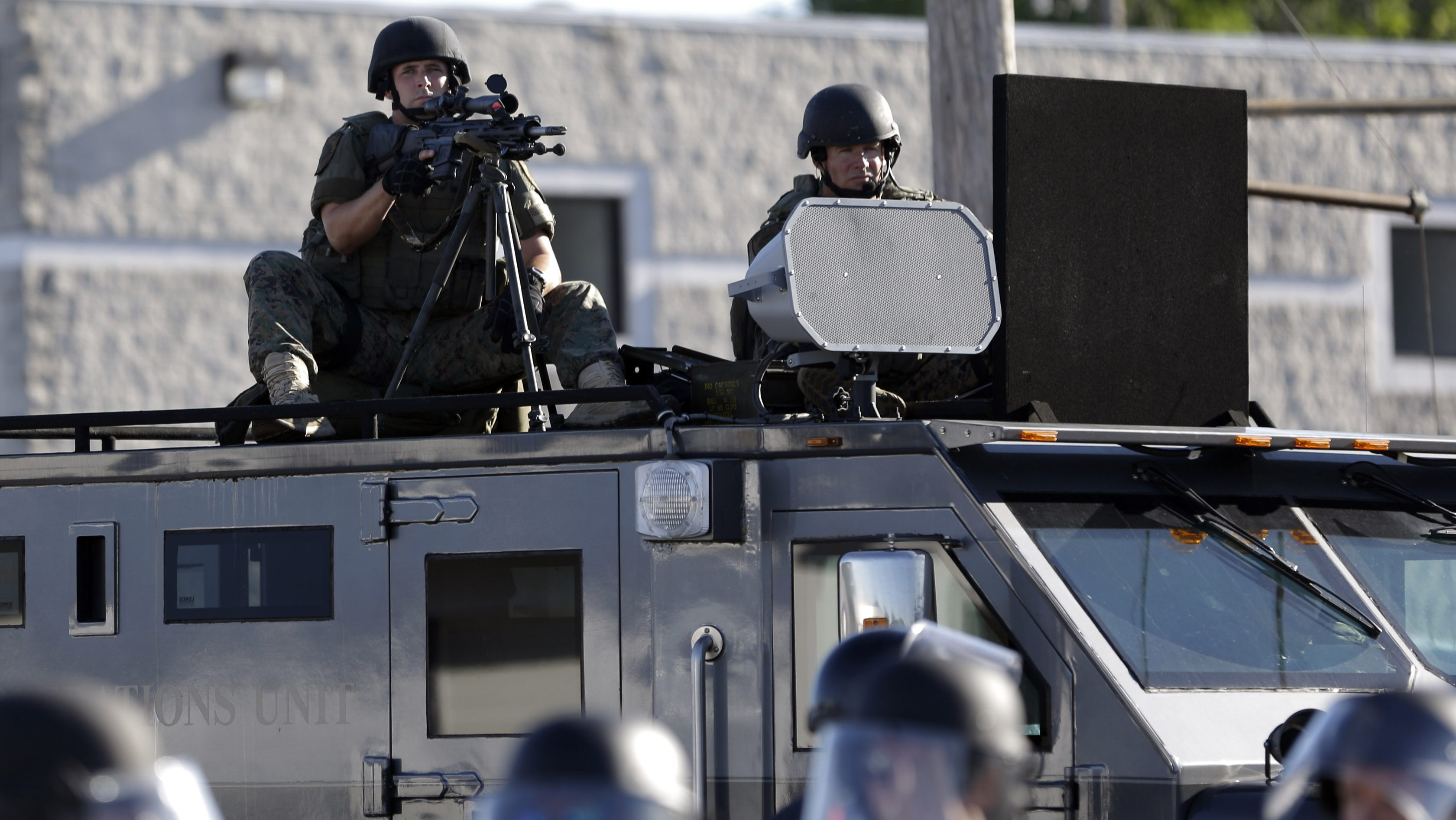 In this Aug. 9, 2014, file photo, a police tactical team moves in to disperse a group of protesters following the shooting of a young black man by a white policeman in Ferguson, Mo. If president-elect Donald Trump keeps his promise, surplus military grenade launchers, bayonets, tracked armored vehicles and high-powered firearms and ammunition will once again be available to state and local U.S. police departments. National police organizations say they'll hold Trump to that promise.(AP Photo/Jeff Roberson, File)