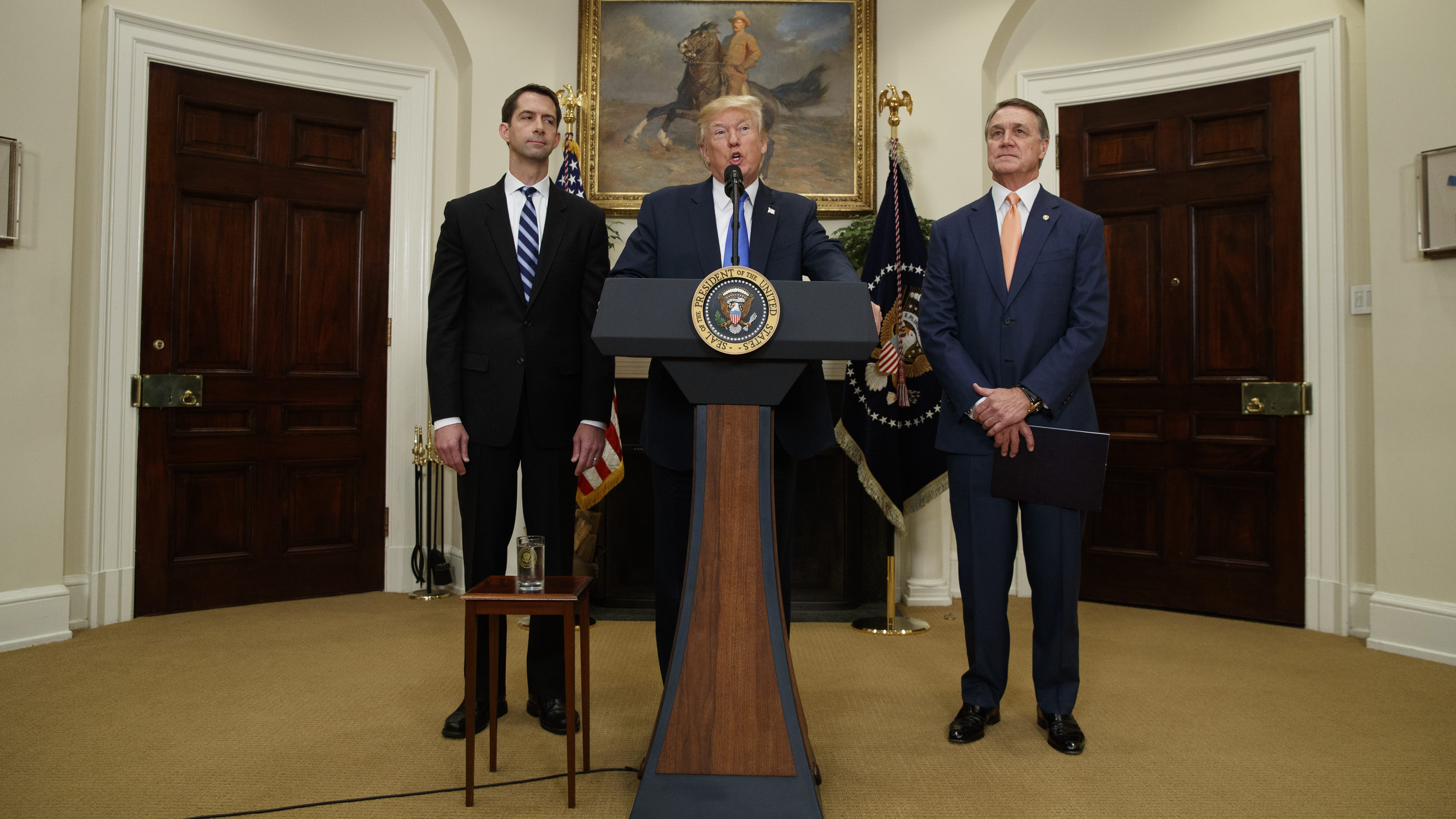 President Donald Trump, flanked by Sen. Tom Cotton, R- Ark., left, and Sen. David Perdue, R-Ga., speaks in the Roosevelt Room of the White House in Washington, Wednesday, Aug. 2, 2017, during the unveiling of legislation that would place new limits on legal immigration. (AP Photo/Evan Vucci)
