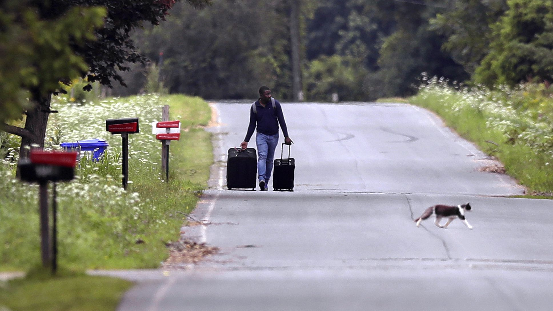Dulne Brutus, of Haiti, tows his luggage down Roxham Road in Champlain, N.Y., while heading to an unofficial border station across from Saint-Bernard-de-Lacolle, Quebec, Monday, Aug. 7, 2017. Officials on both sides of the border first began to notice last fall, around the time of the U.S. presidential election, that more people were crossing at Roxham Road. Since then the numbers have continued to climb.