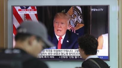 People walk by a TV screen showing a local news program reporting with an image of U.S. President Donald Trump
