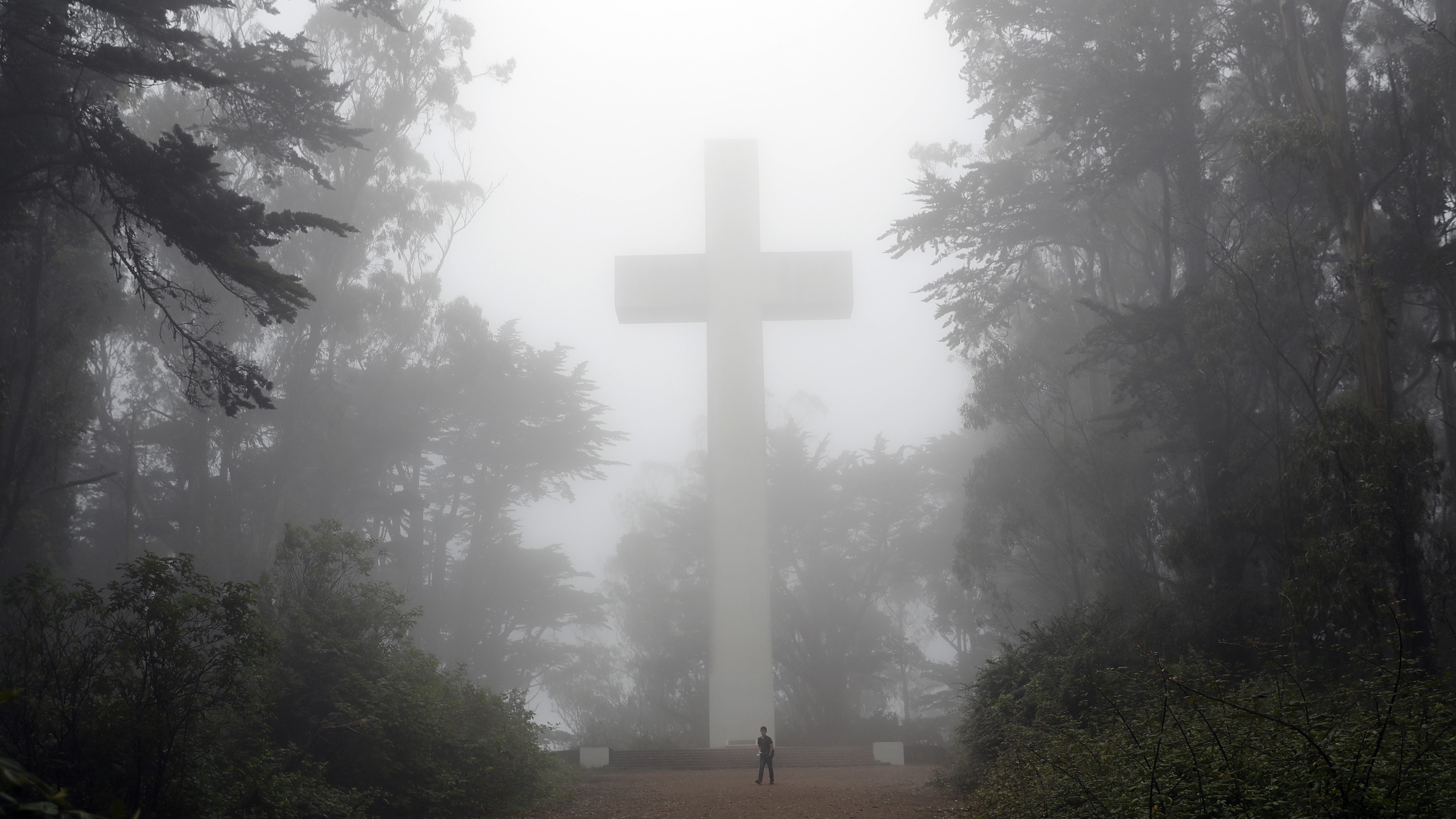 A visitor walks under a fog-covered cross on Mount Davidson, Friday, Aug. 11, 2017, in San Francisco.