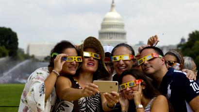 A family takes a selfie wearing a safety glasses to watch phases of solar eclipse, at the National Mall in Washington, Monday, Aug. 21, 2017.