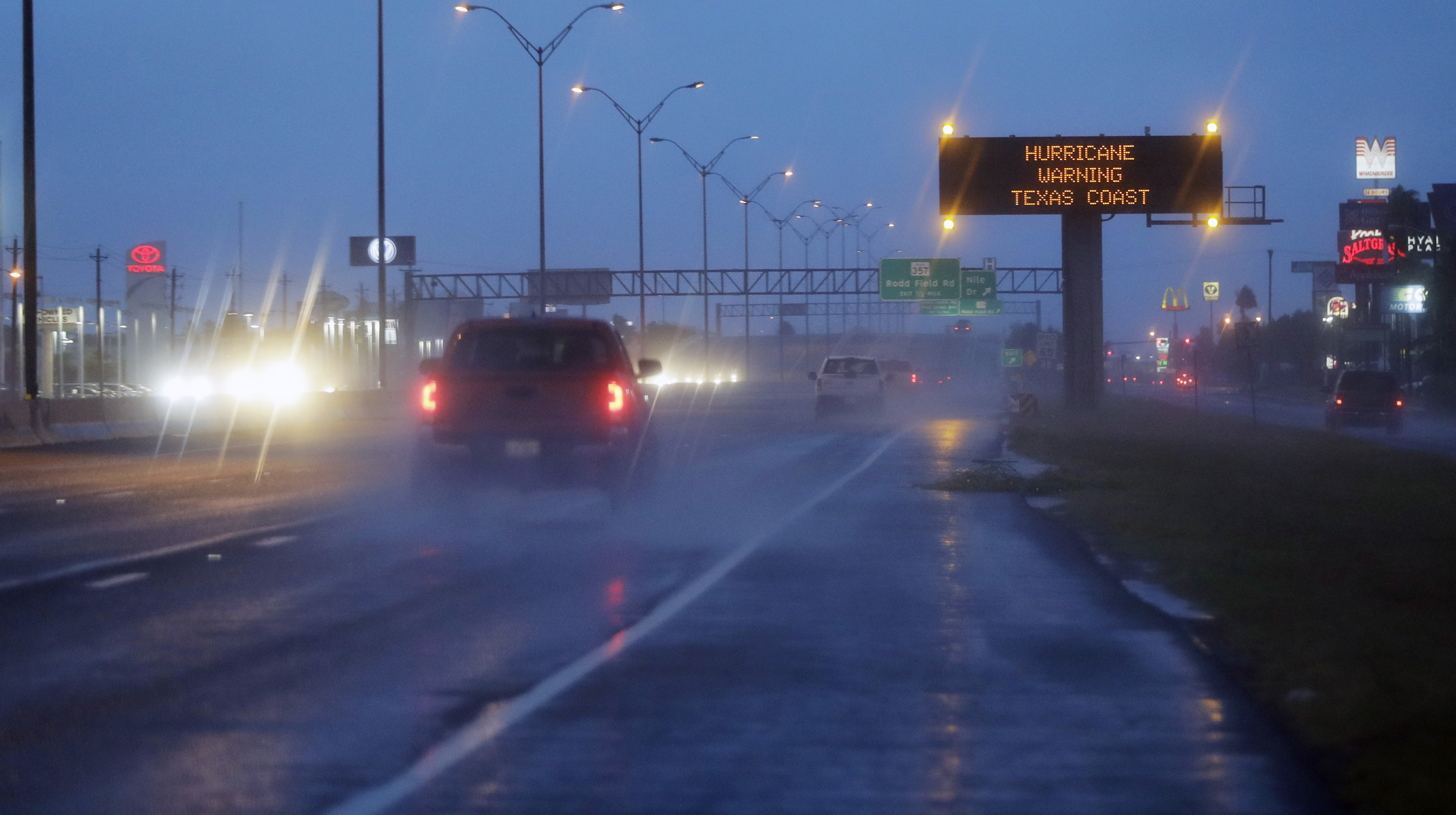 """Motorists pass a warning sign  as Hurricane Harvey approaches the Gulf Coast area Friday, Aug. 25, 2017, in Corpus Christi, Texas.  The slow-moving hurricane could be the fiercest such storm to hit the United States in almost a dozen years. Forecasters labeled Harvey a """"life-threatening storm"""" that posed a """"grave risk"""" as millions of people braced for a prolonged battering. (AP Photo/Eric Gay)"""