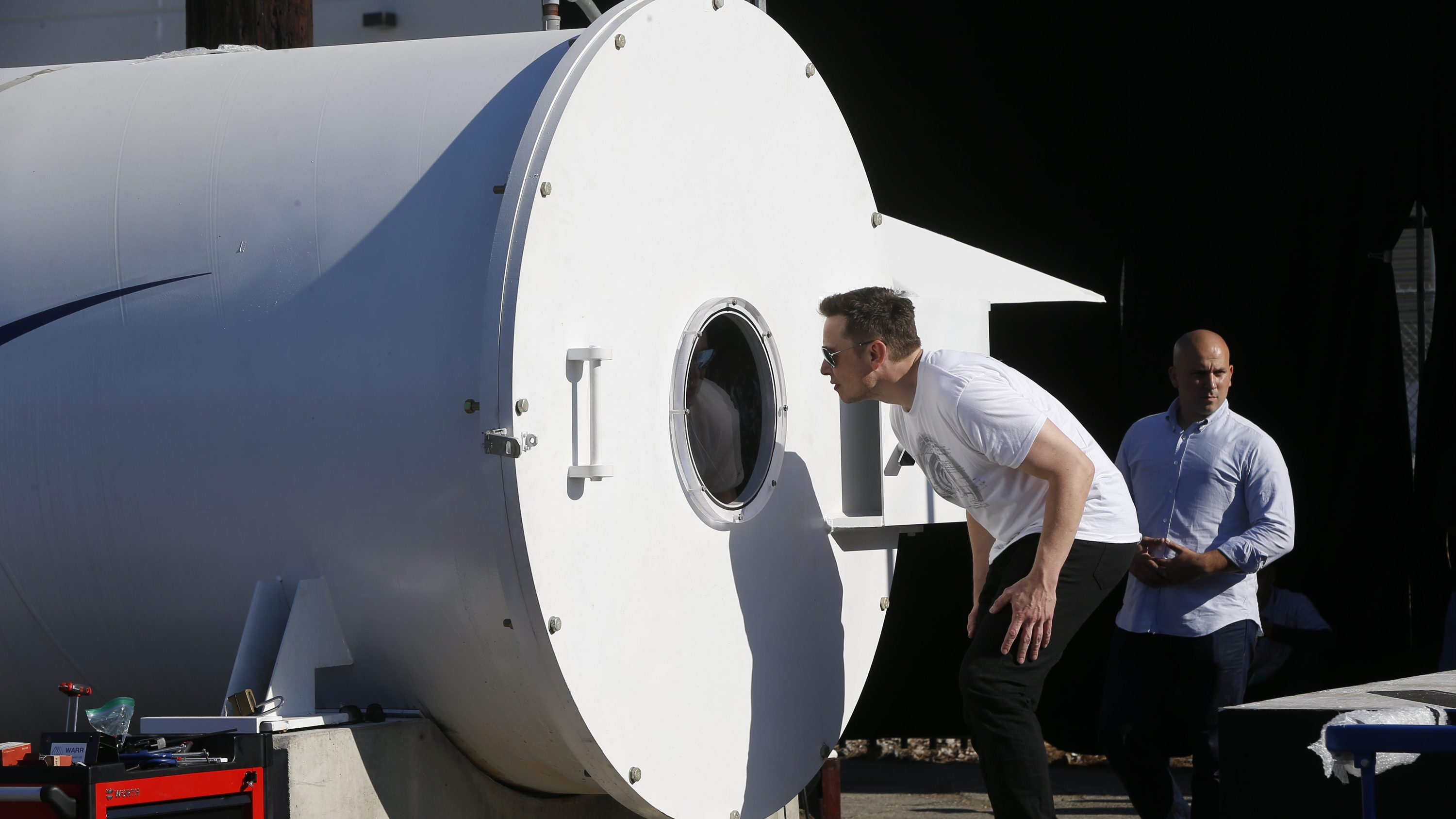Telsa CEO Elon Musk peaks inside the Hyperloop track door at the Hyperloop Pod Competition II at SpaceX's Hyperloop track in Hawthorne, Calif., Sunday, Aug. 27, 2017. The Hyperloop system built by SpaceX is approximately one mile in length with a six-foot outer diameter. The WARR team from Tech University Munich won the Hyperloop Pod Competition II with a peak speed of 324 kilometers per hour (201 mph).