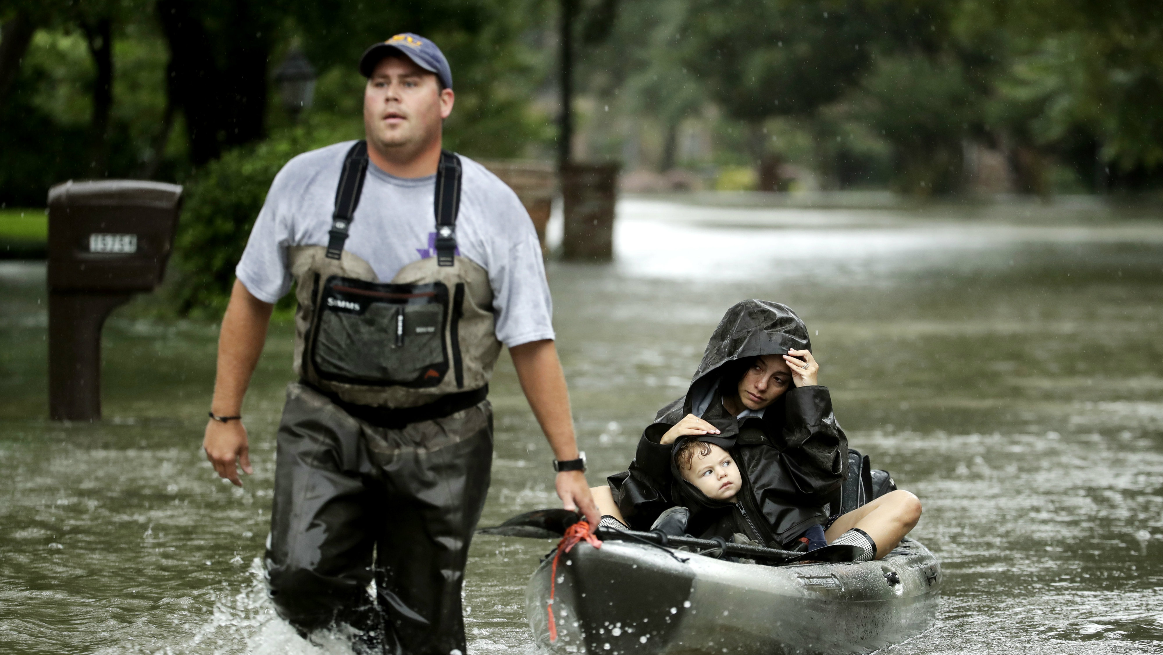 Man rescuing a woman and a child on a kayak.