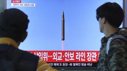 """People watch a TV screen showing a file footage of North Korea's missile launch, at the Seoul Railway Station in Seoul, South Korea, Tuesday, Aug. 29, 2017. North Korea fired a ballistic missile from its capital Pyongyang that flew over Japan before plunging into the northern Pacific Ocean, officials said Tuesday, an especially aggressive test-flight that will rattle an already anxious region.The signs read """" A National Security Council meeting will be held."""""""