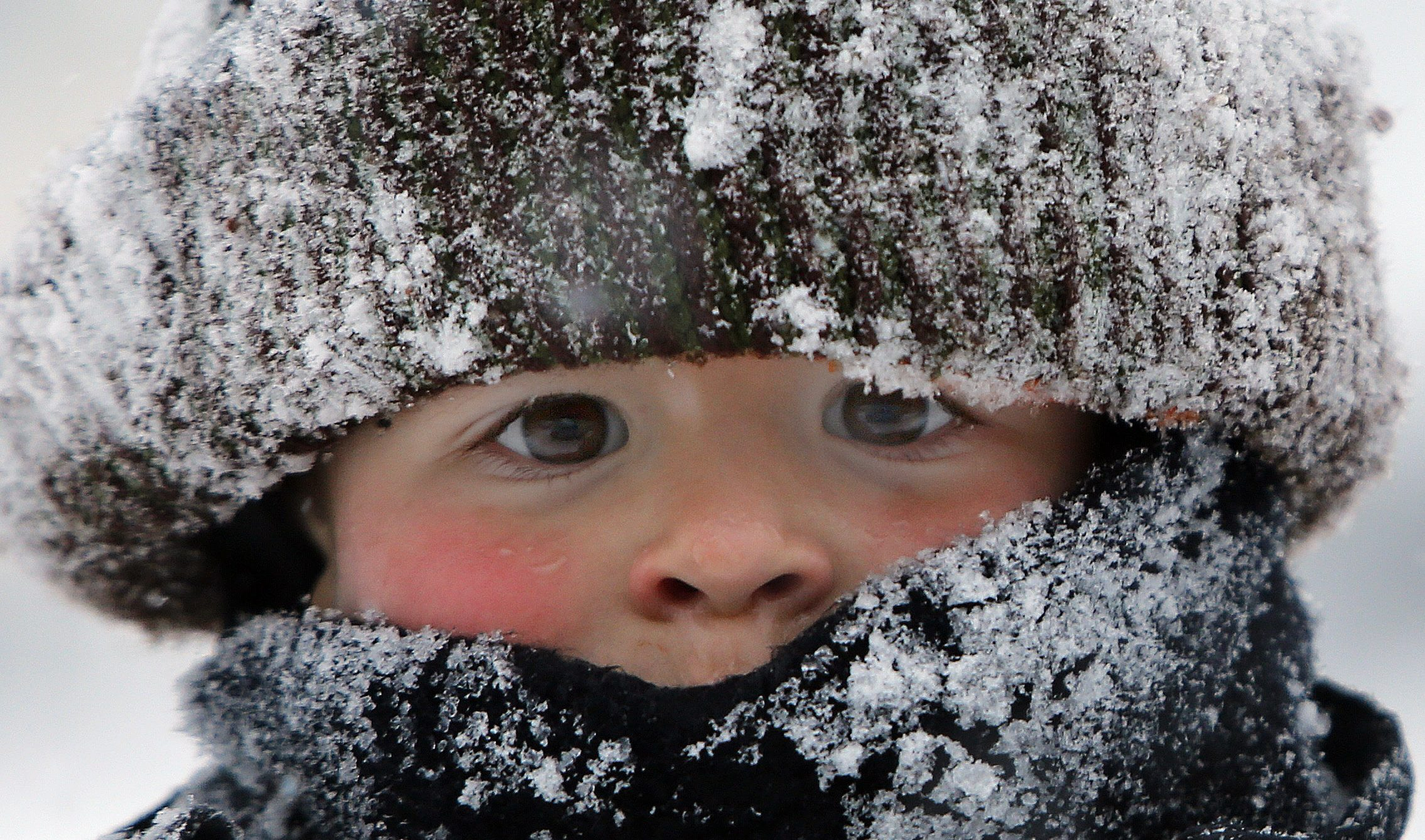 Will Annicchiarico is bundled up as he plays in the snow following a snowstorm Tuesday, Jan. 27, 2015, in Concord, N.H. A storm packing blizzard conditions spun up the East Coast early Tuesday, pounding parts of coastal New Jersey northward through Maine with high winds and heavy snow. (AP Photo/Jim Cole)