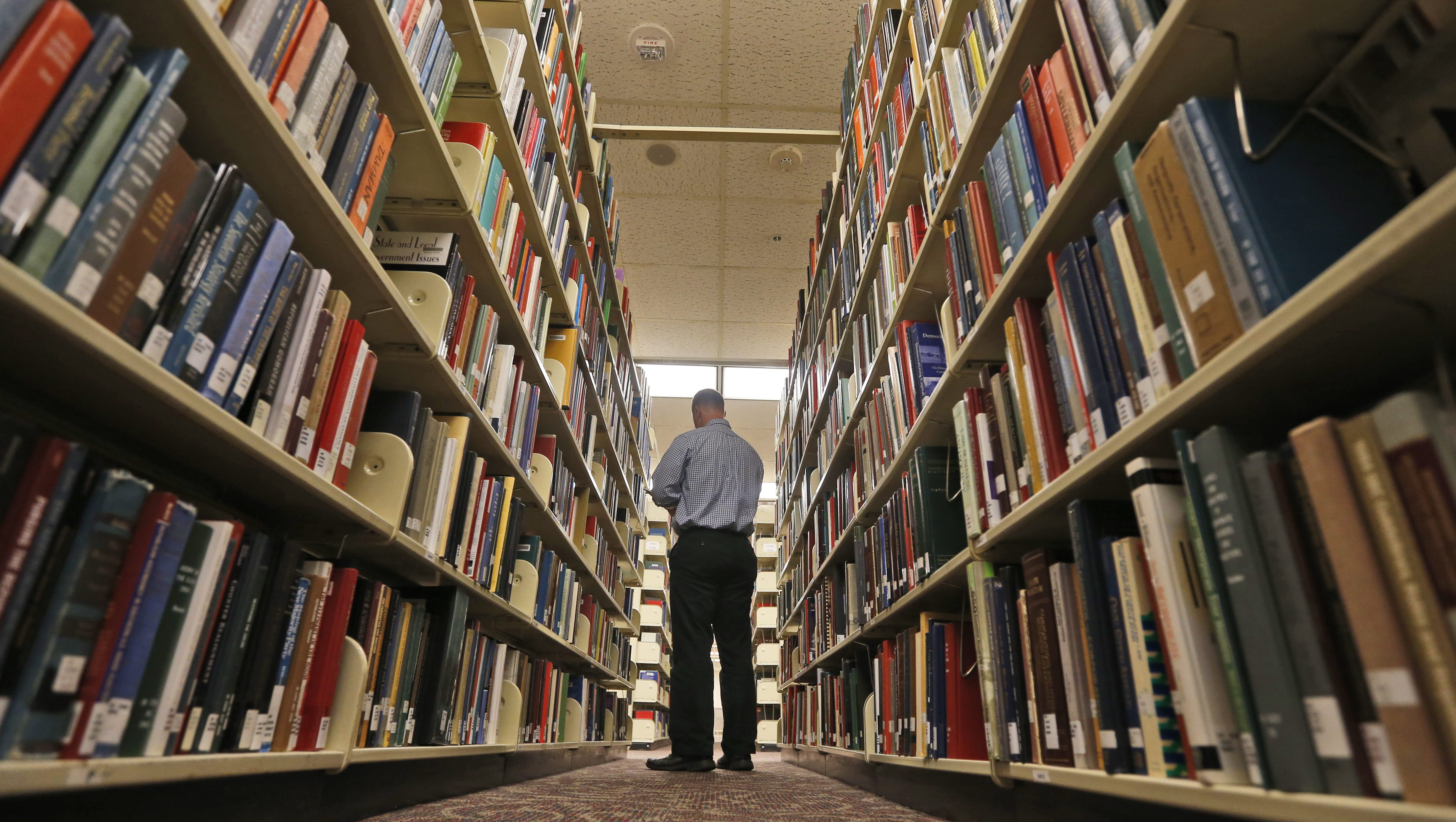 A visitor looks over books in the classic area of the renovated James Branch Cabell library on the campus of Virginia Commonwealth University  in Richmond, Va., Thursday, April 28, 2016.   (AP Photo/Steve Helber)