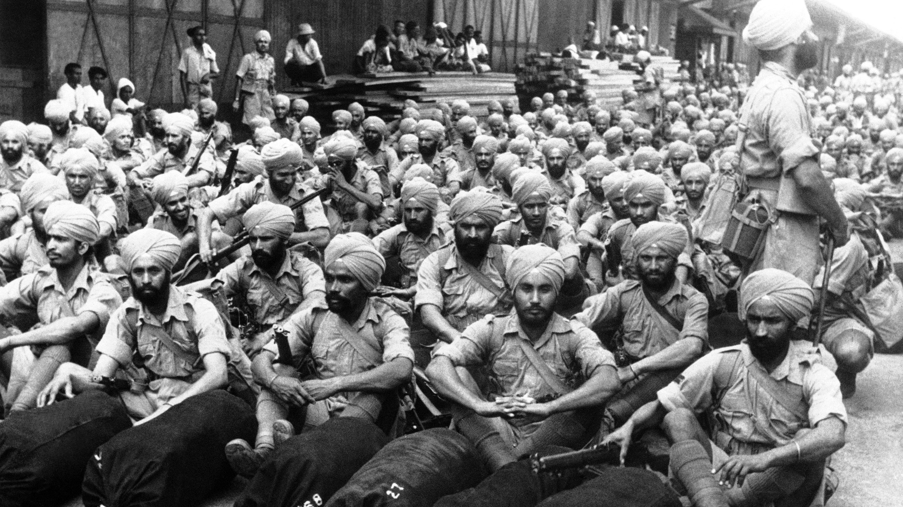 British Indian troops sit complacently on the wharf after their arrival in Singapore on March 31, 1941 to augment Royal crown forces on the Malayan Peninsula. (AP Photo)