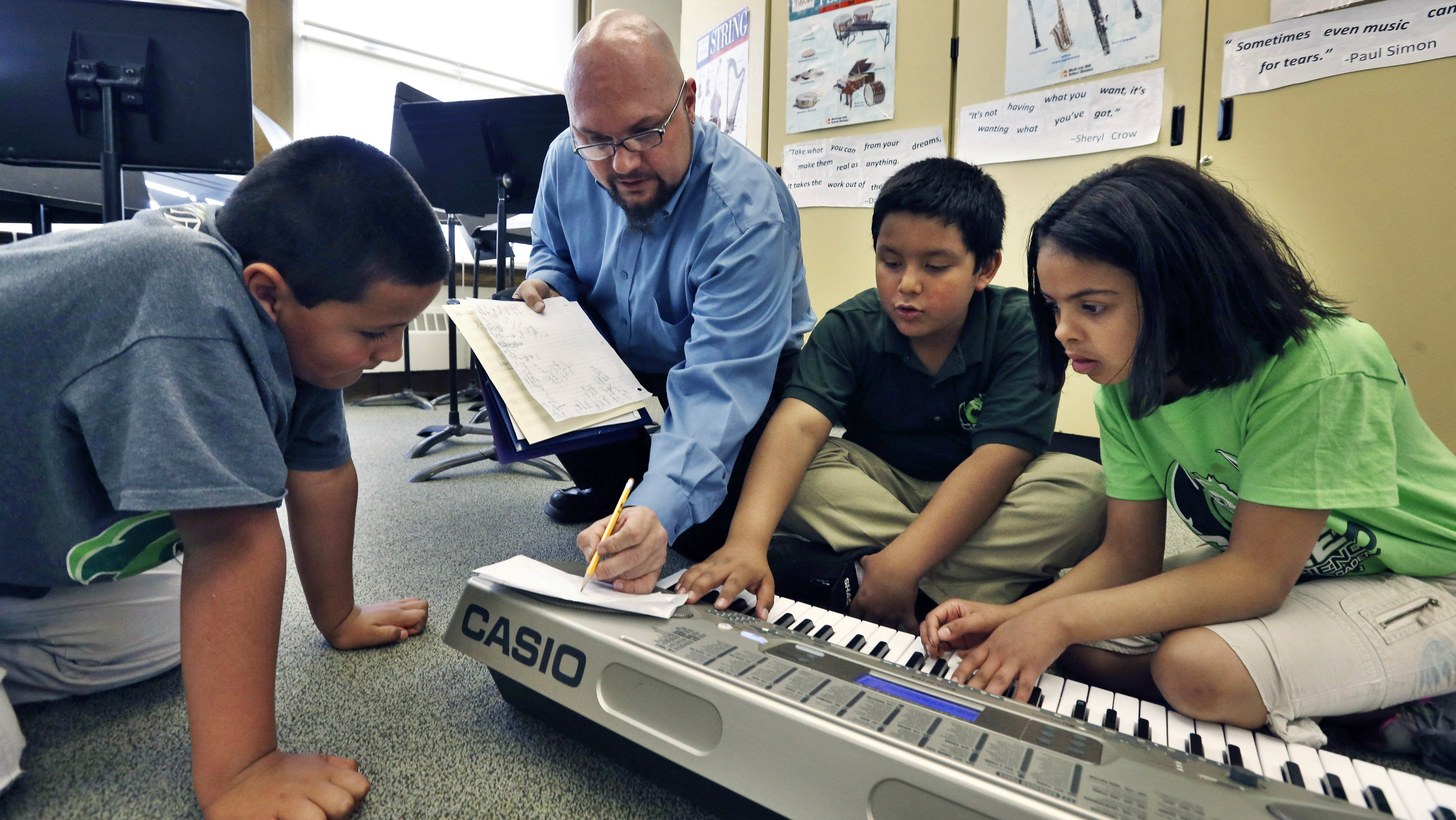 Music teacher teaching kids how to play the electric piano.