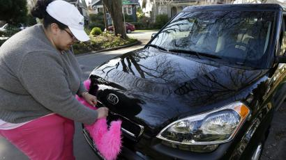 Lyft Driver adjusting the pink mustache on her car.