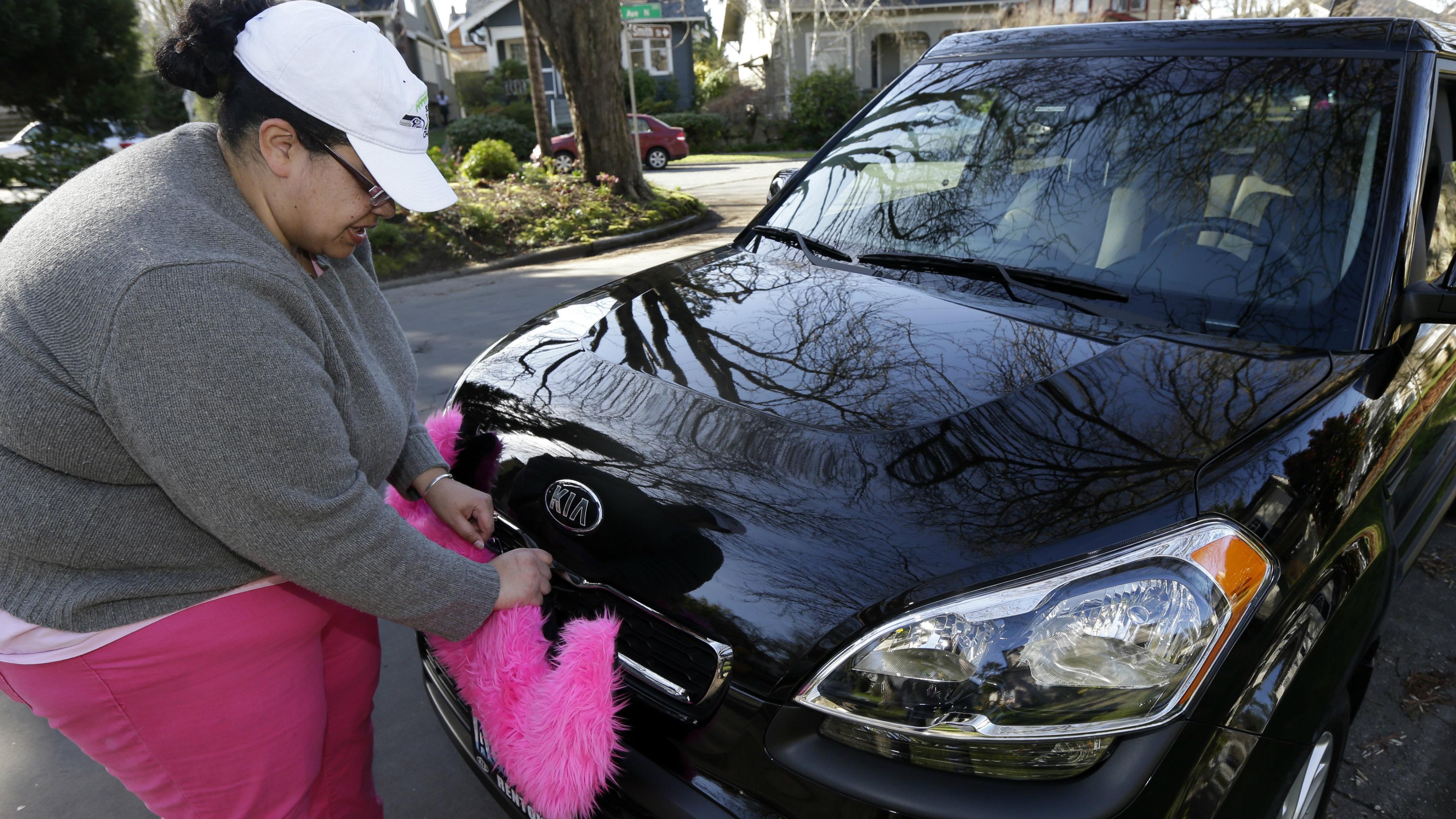 Lyft Driver adjusting the pink mustache on her car.