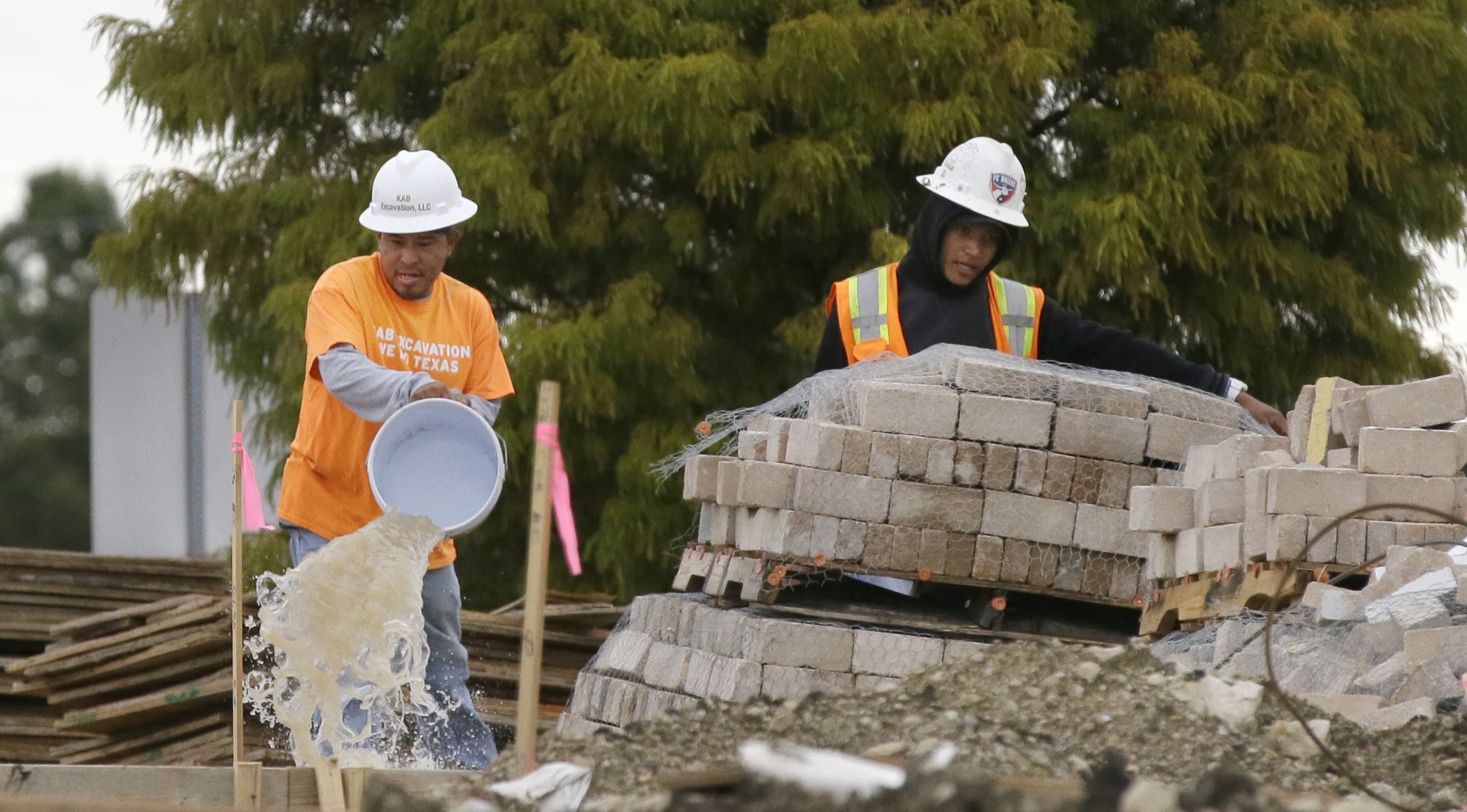 Workers bucket out water from a waterlogged construction site in the Dallas suburb of Richardson, Texas, Monday, Oct. 26, 2015. After a weekend of drenching storms that were remnants of Hurricane Patricia, the week in Texas starts clear without the death or devastation of torrential rain and floods that hit the state earlier in the year. (AP Photo/LM Otero)