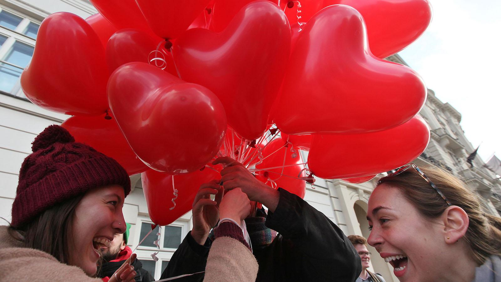 girls hold heart-shaped balloons