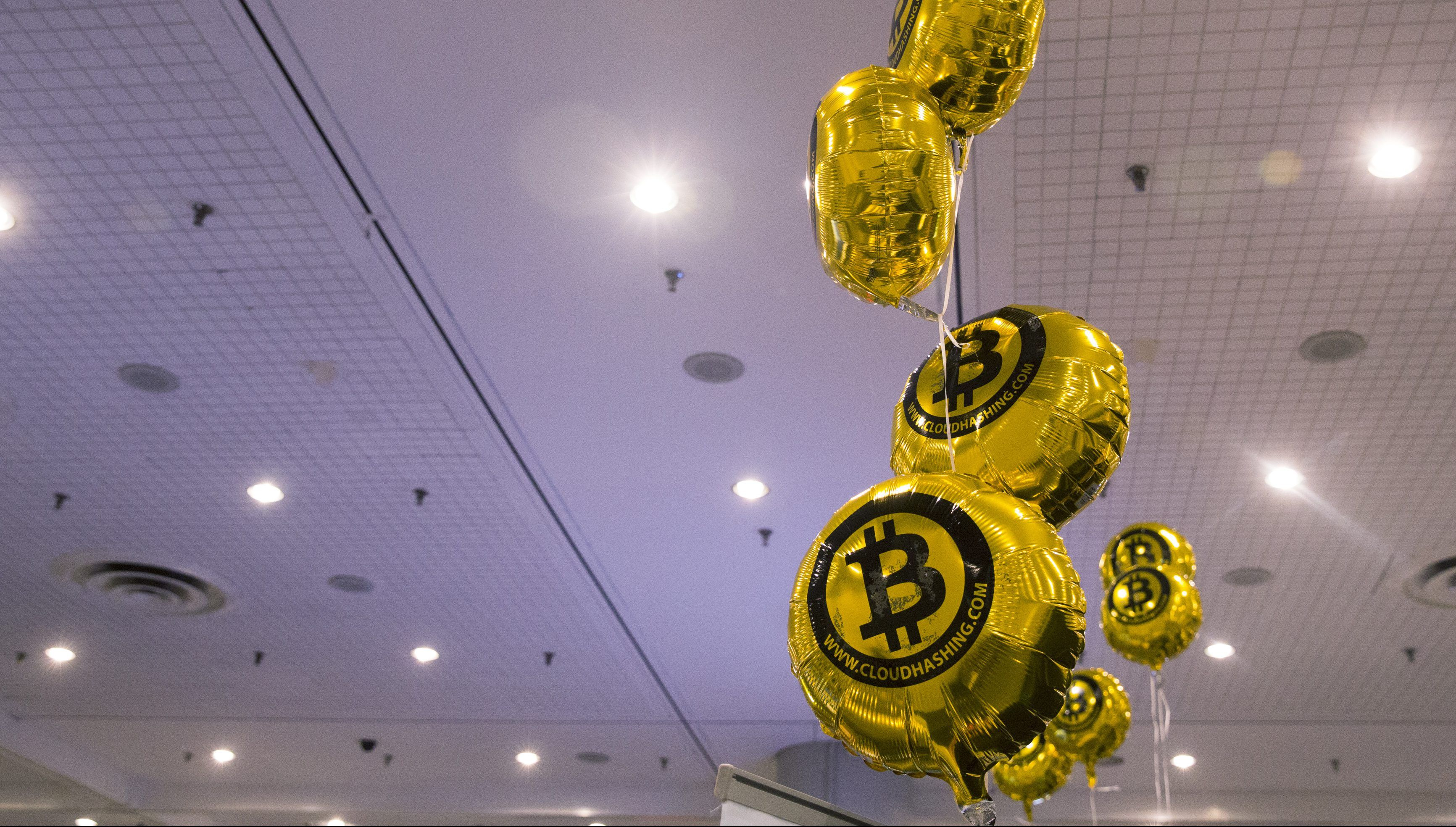 """Bitcoin themed balloons float in the air during the """"Inside Bitcoins: The Future of Virtual Currency Conference"""" in New York April 8, 2014."""