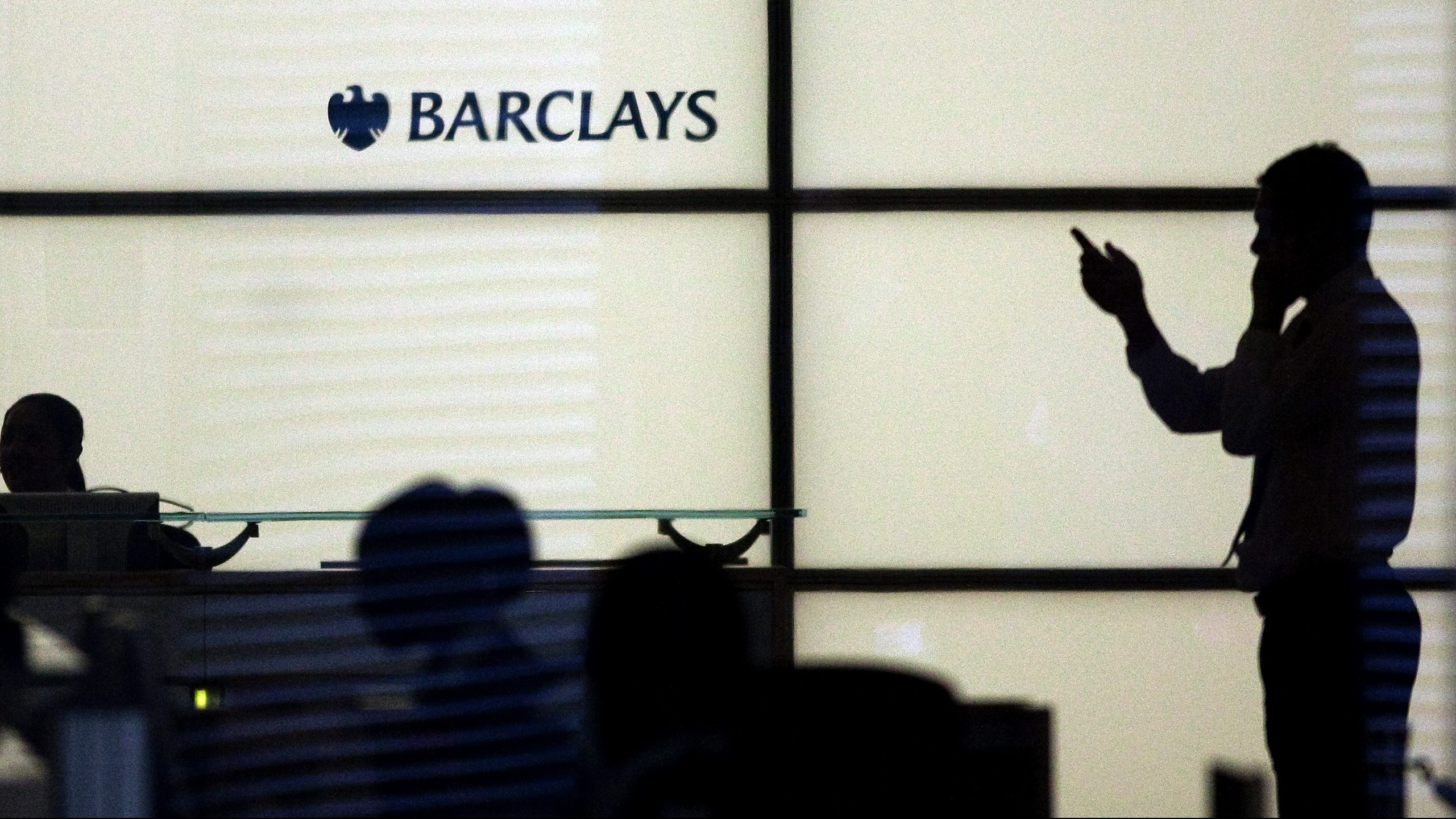 A man gestures whilst speaking on a mobile telephone at Barclays Bank in the financial district of Canary Wharf in London January 19, 2009. Britain unveiled a second support package on Monday for struggling banks to try and get lending flowing again in an economy lurching into its first recession since the early 1990s.