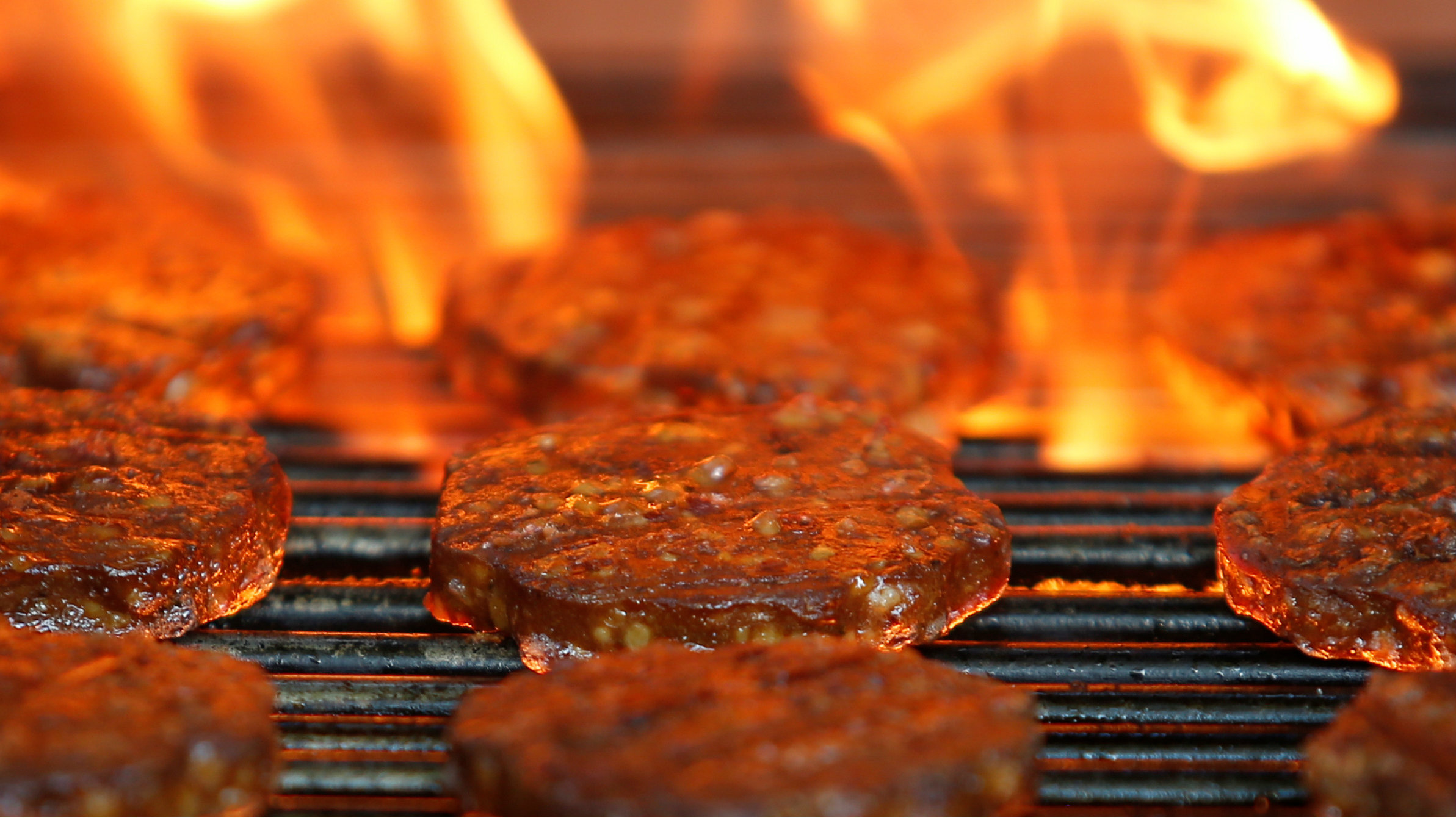 Burgers are cooked over a flame on a grill