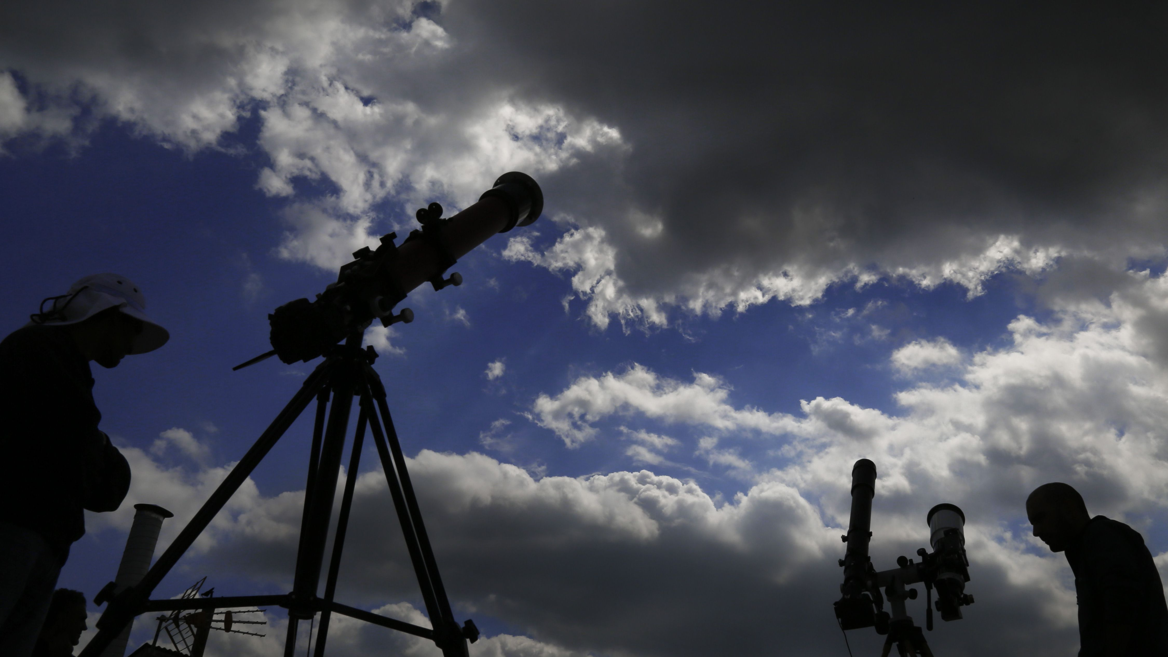 Two men sets up a telescopes as they watch an eclipse of the sun at capital Nicosia, Cyprus, Friday, March 20, 2015. An eclipse is darkening parts of Europe on Friday in a rare solar event that won't be repeated for more than a decade.