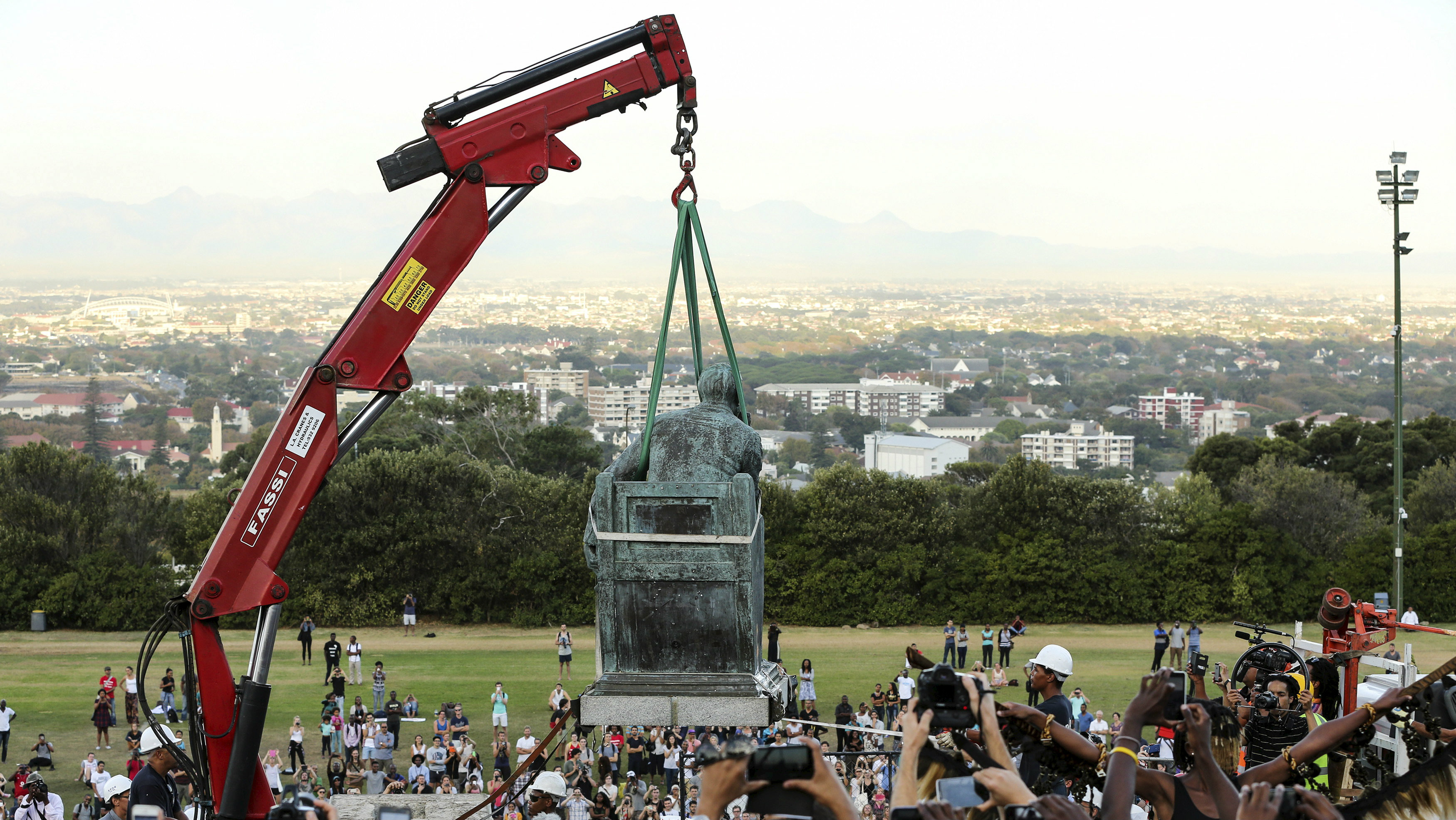 Students cheer as the statue of Cecil John Rhodes is removed from the University of Cape Town (UCT), April 9, 2015. The statue at the university, one of Africa's top academic institutions, has been covered up for the past few weeks as both white and black students regularly marched past with #Rhodesmustfall placards calling for its removal. They believe it is a symbol of the racism against blacks that prevails in South Africa two decades after the end of oppressive white-minority rule.