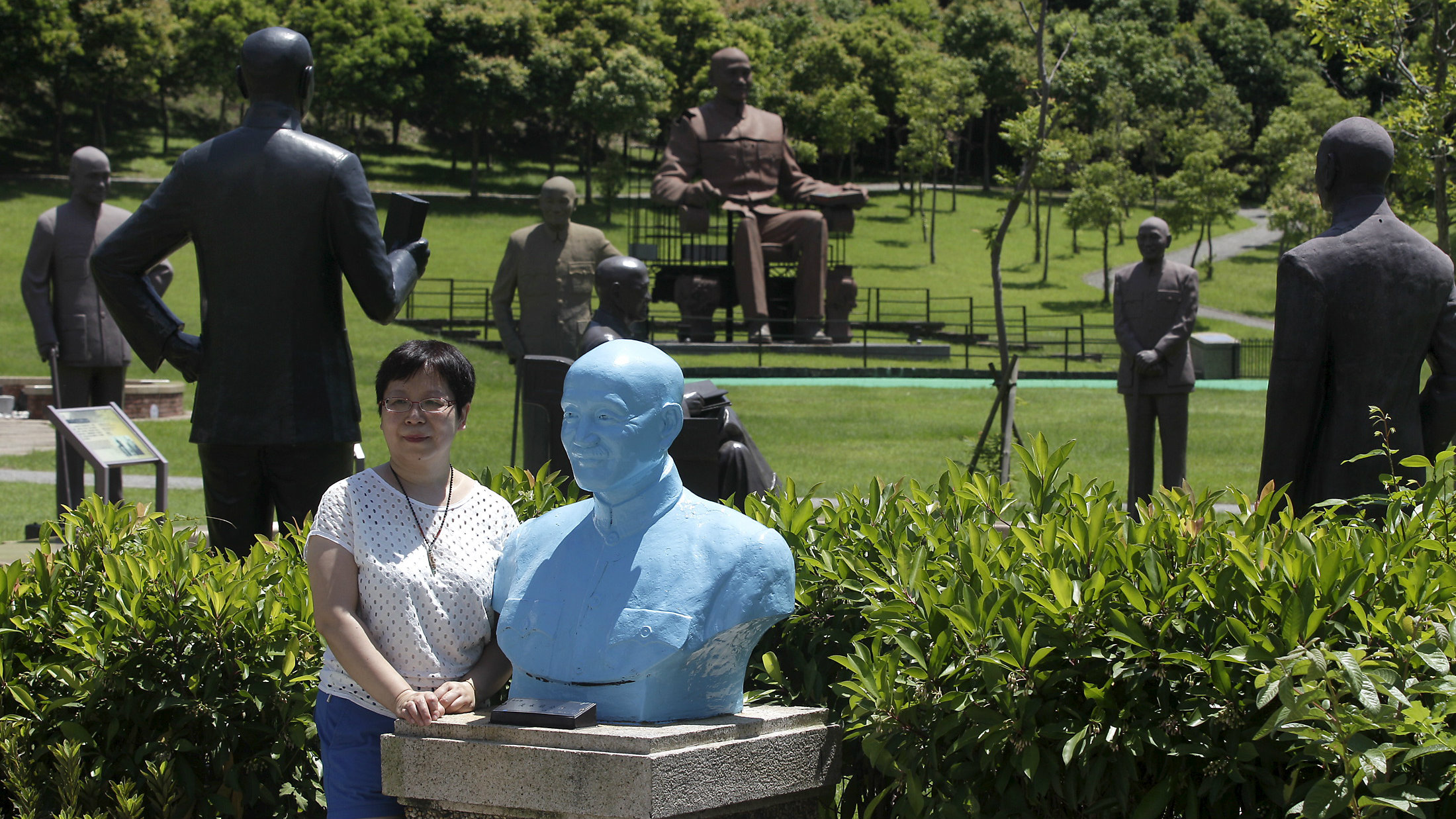 A woman poses for photographs next to a bust of the late president and Nationalist leader Chiang Kai-shek in Taoyuan, northern Taiwan, July 5, 2015. Dumped outside Chiang Kai-shek's mausoleum in Taiwan are nearly 200 unwanted statues of the Nationalist Party hero, a suggestion of the punishment his party faces in January elections for pushing the self-ruled island too close to political foe China. Cast in bronze and in different shades of red, brown, grey and blue, the generalissimo is saluting, holding a book, leaning on a cane, sitting regally or perched on a plinth - a peaceful if surreal gathering that belies the disarray of the party it represents.