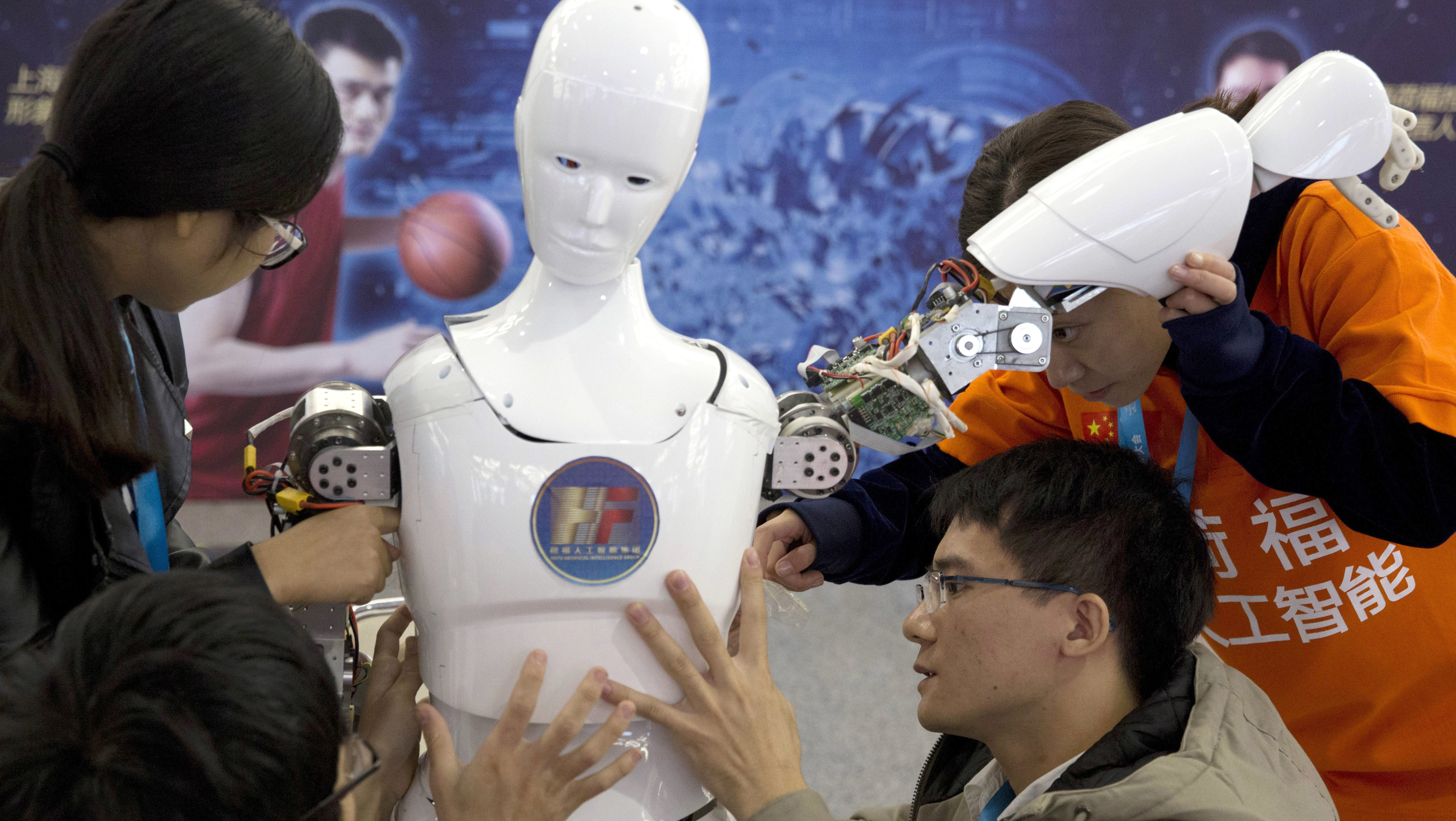 Chinese students work on the Ares, a humanoid bipedal robot designed by them with fundings from a Shanghai investment company, displayed during the World Robot Conference in Beijing. China's government announced Thursday, July 21, 2017, a goal of transforming the country into a global leader in artificial intelligence in just over a decade, putting additional political support behind growing investment by Chinese companies in developing self-driving cars and other advances.