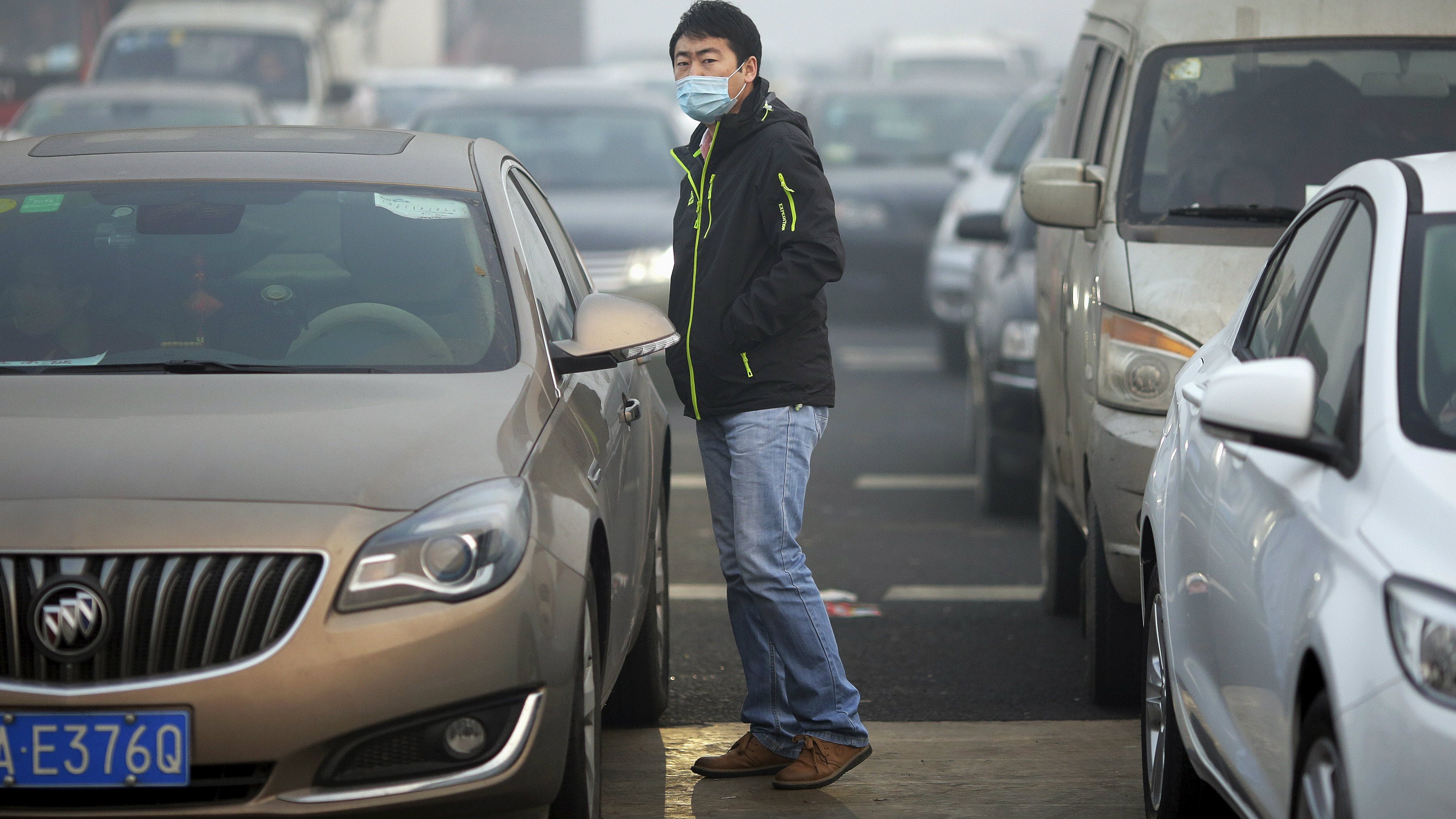 A driver wears a mask between vehicles stranded on a highway between Beijing and Hebei province, China, that is closed due to smog on an extremely polluted day November 30, 2015.