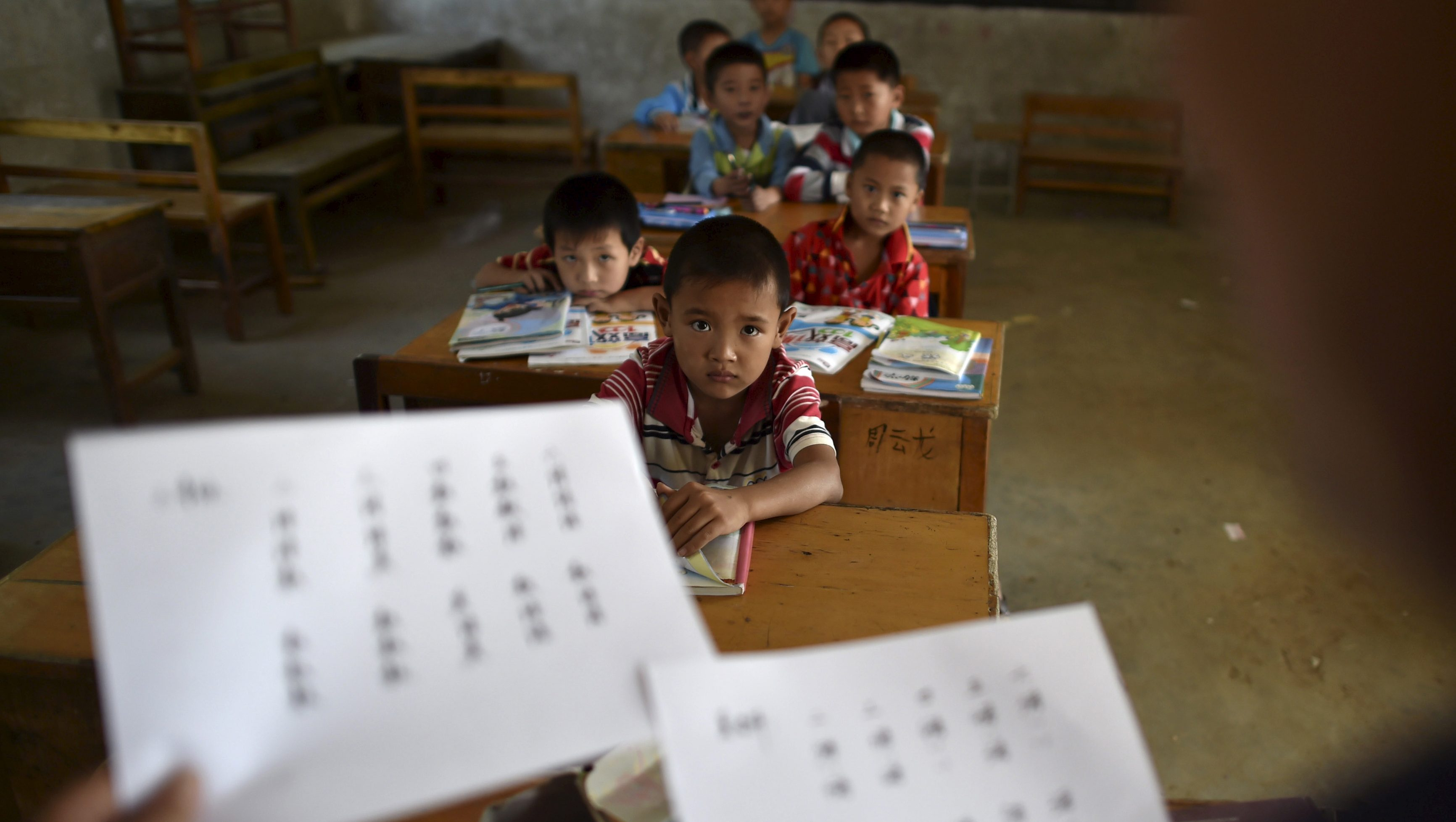 "Students look at their teacher holding papers of the new curriculum at a classroom of Dalu primary school in Gucheng township of Hefei, Anhui province, China, September 8, 2015. The school, opened in 2006 and has never acquired a legal license, may face a shutdown order from the government. There are currently over 160 students in the school, mostly ""leftover children"", whose parents left their hometown to earn a living, local media reported. Picture taken September 8, 2015."