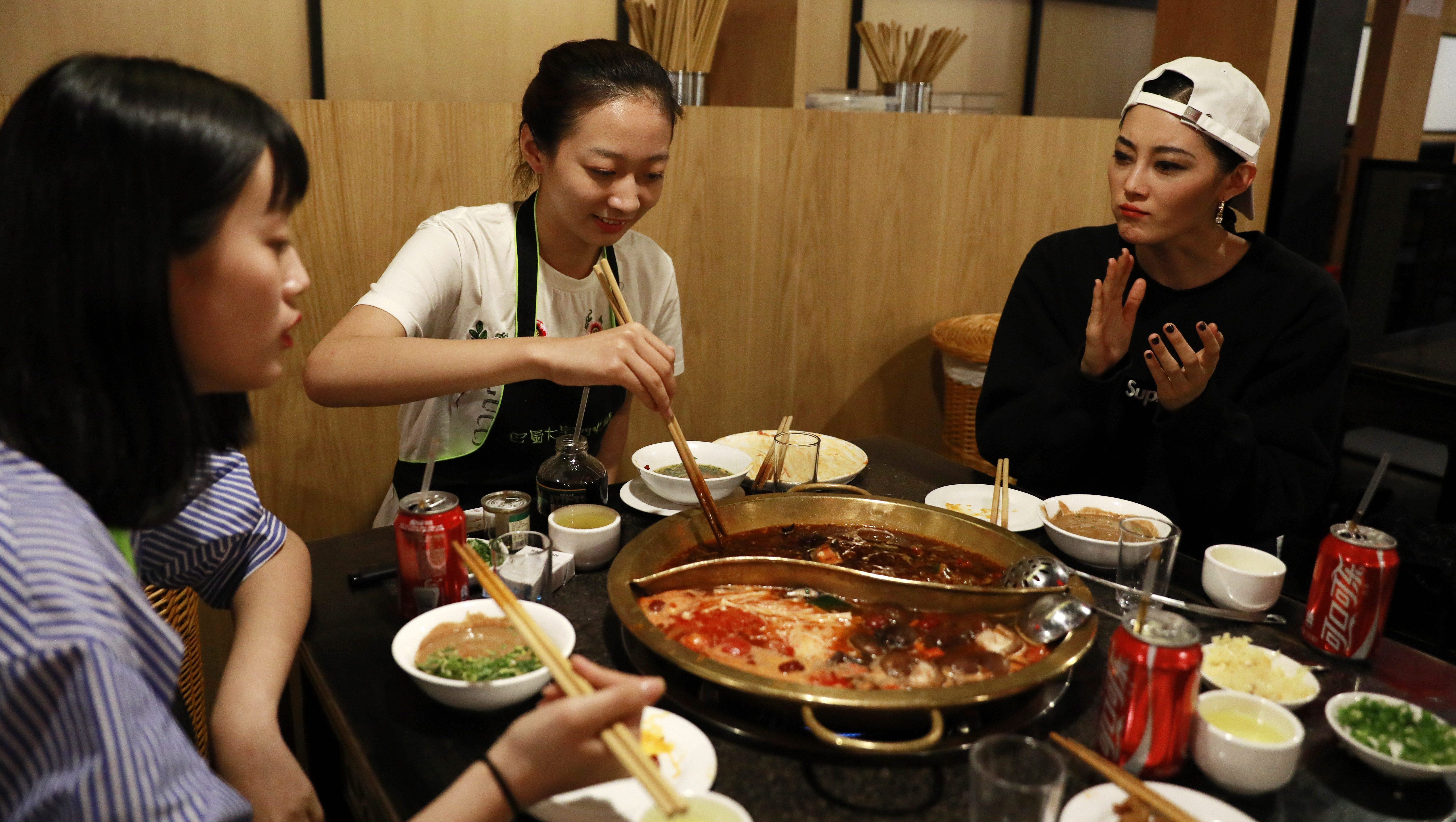 Chinese model Sun Yichao (R) and her juniors Jiang Ruiqi (L) and Li Yuzu from the same modelling agency have a hotpot dinner at a restaurant after the Melody Cashmere show during the Mercedes-Benz China Fashion Week at the Beijing Hotel banquet hall venue in Beijing, China, 29 March 2017. One of China's most promising up and coming fashion model, the 23-year-old Sun Yichao is a striking figure on the runway. At 1.79 metres tall, the svelte model with beautiful chiseled features is high in demand domestically and abroad, having walked the catwalks of Paris, Milan and New York's fashion weeks for major brands like Christian Dior and Chanel. She was also one of the recipients of the 'China Top Ten Professional Fashion Model Award' in 2016.