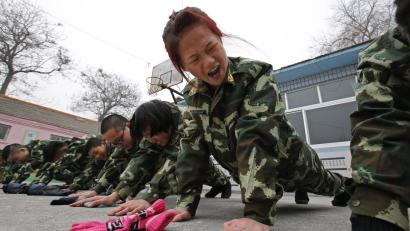 Students receive a group punishment during a military-style close-order drill class at the Qide Education Center in Beijing February 19, 2014. The Qide Education Center is a military-style boot camp which offers treatment for internet addiction. As growing numbers of young people in China immerse themselves in the cyber world, spending hours playing games online, worried parents are increasingly turning to boot camps to crush addiction. Military-style boot camps, designed to wean young people off their addiction to the internet, number as many as 250 in China alone. Picture taken February 19, 2014. REUTERS/Kim Kyung-Hoon (CHINA - Tags: SOCIETY) ATTENTION EDITORS - PICTURE 12 OF 33 FOR PACKAGE 'CURING CHINA'S INTERNET ADDICTS' TO FIND ALL IMAGES SEARCH 'INTERNET BOOT CAMP' - RTR3WL7U