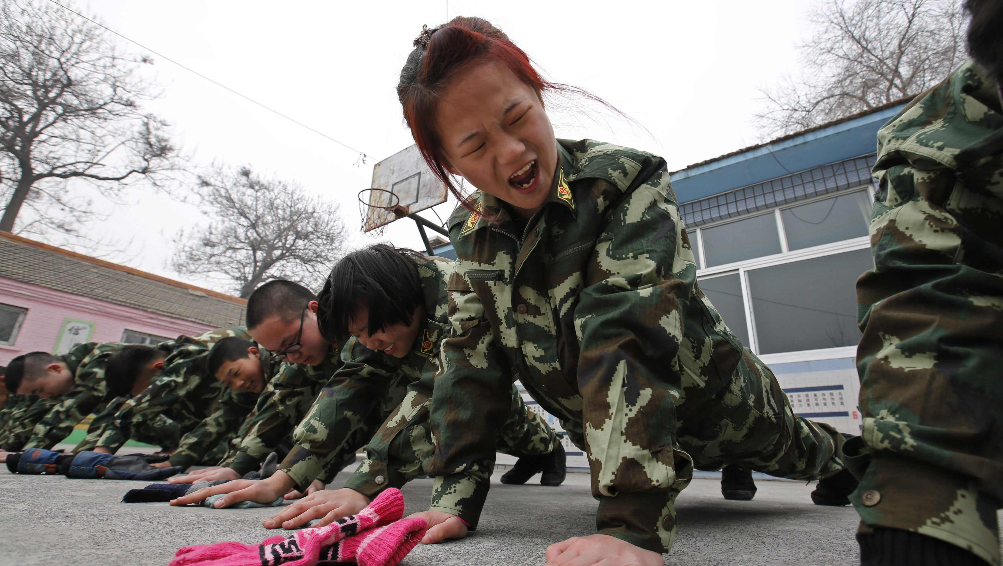 Students receive a group punishment during a military-style close-order drill class at the Qide Education Center in Beijing February 19, 2014. The Qide Education Center is a military-style boot camp which offers treatment for internet addiction. As growing numbers of young people in China immerse themselves in the cyber world, spending hours playing games online, worried parents are increasingly turning to boot camps to crush addiction. Military-style boot camps, designed to wean young people off their addiction to the internet, number as many as 250 in China alone. Picture taken February 19, 2014.