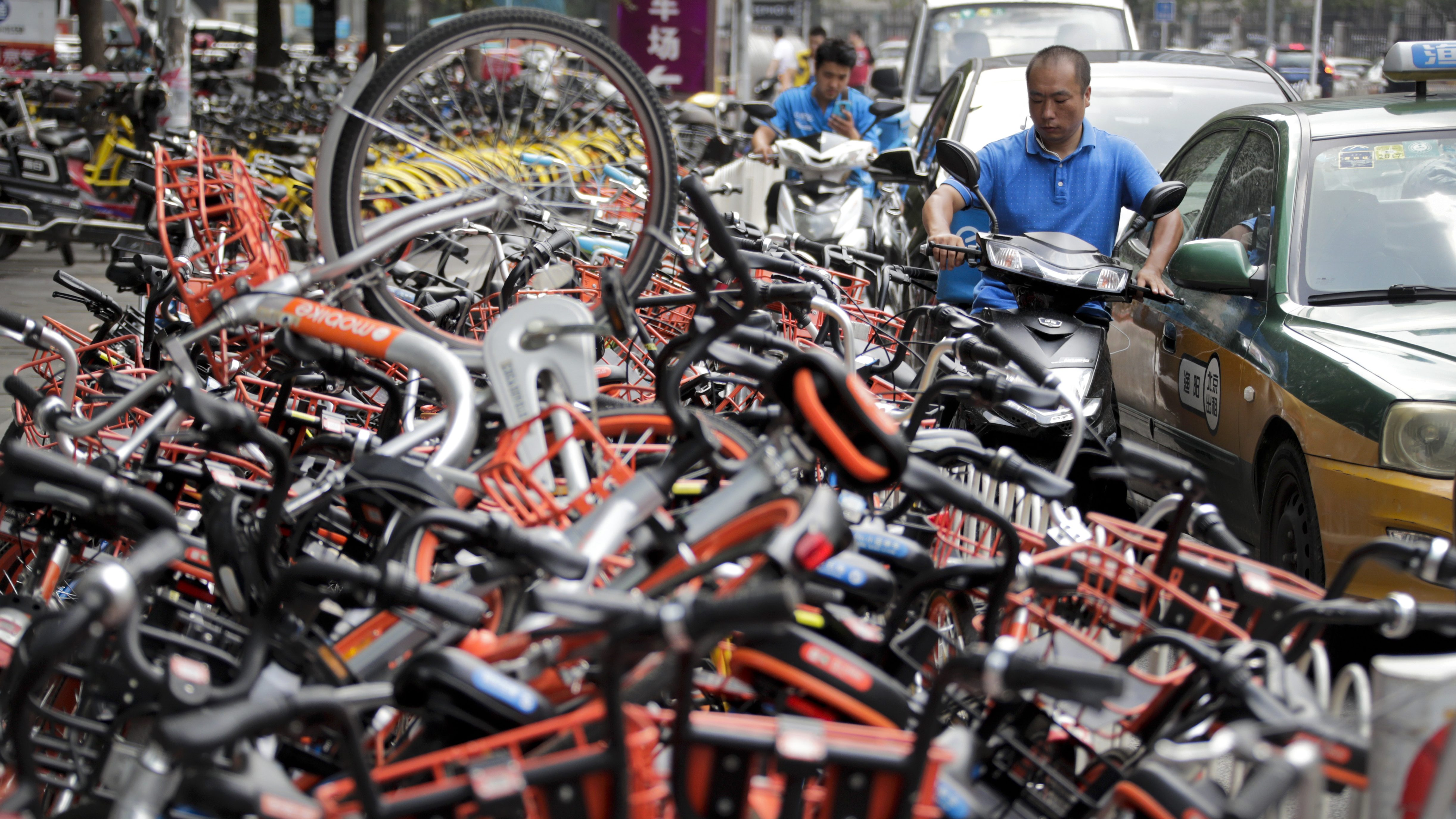 A man on his electric motorbike scooter tries to pass a busy traffic car lane as a stack of shared bicycles block the cycle lane on a street in Beijing, Monday, Aug. 14, 2017. Chinese authorities has issued nationwide guidelines to regulate the bike-sharing services which have boomed but created management issues as millions of bikes clogged the sidewalks in major cities across China. (AP Photo/Andy Wong)