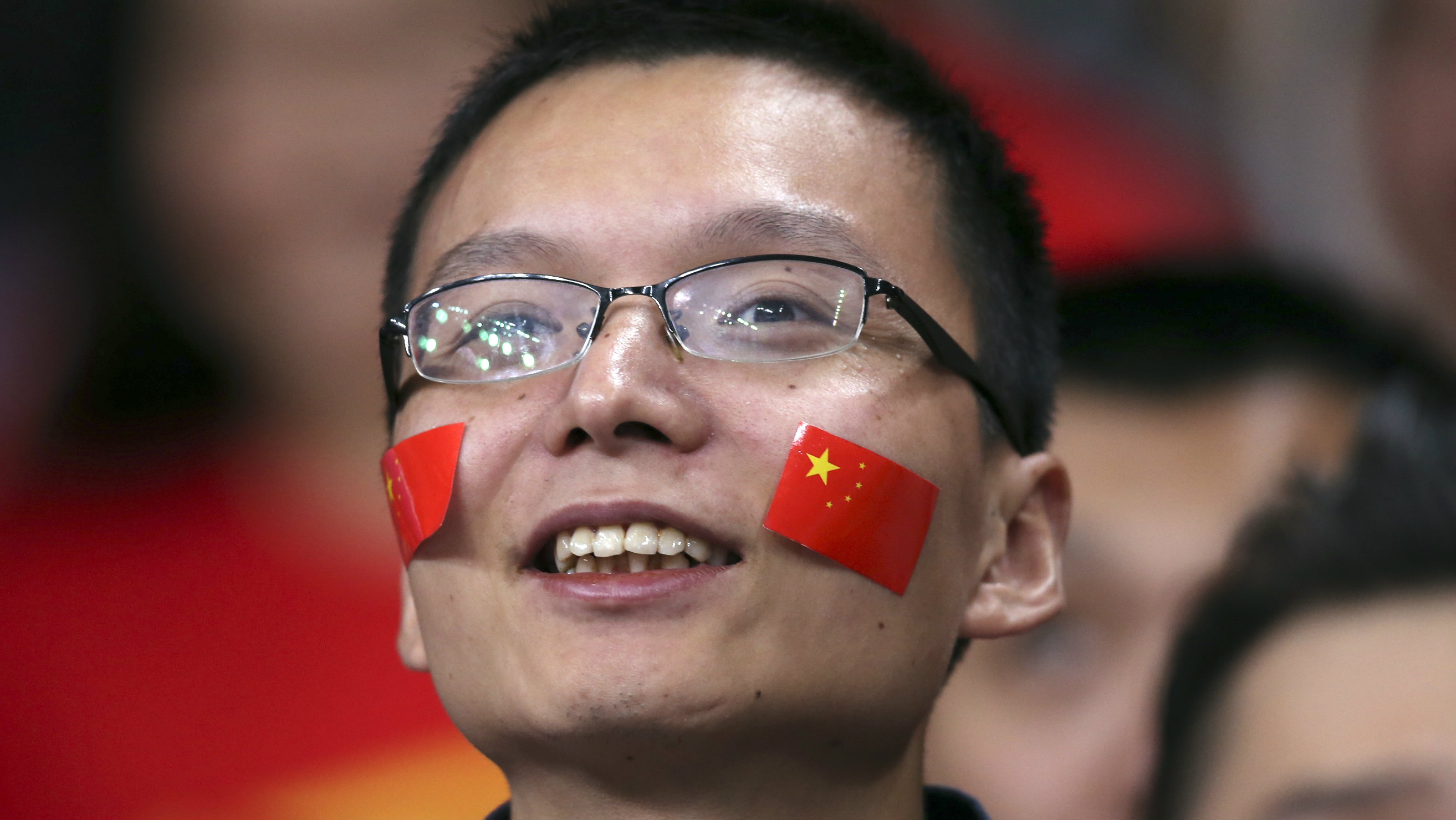 A man with Chinese national flags stuck to his cheeks smiles during their women's Group B volleyball match against Serbia at the London 2012 Olympic Games at Earls Court in London July 28, 2012.
