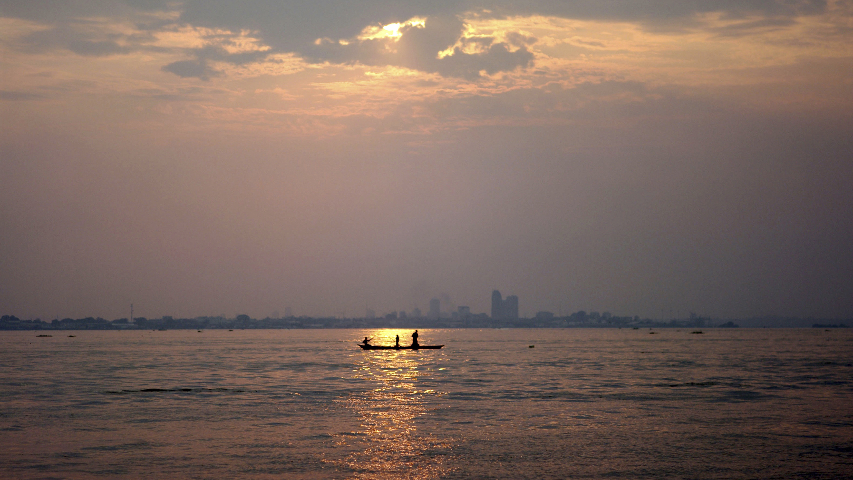 A wooden pirogue sails at dusk on the Congo River against the backdrop of high rises in the Democratic Republic of Congo's capital Kinshasa, March 7, 2010. Picture taken March 7, 2010. REUTERS/Katrina Manson (DEMOCRATIC REPUBLIC OF CONGO - Tags: SOCIETY ENVIRONMENT CITYSCAPE) - RTR2BDRC