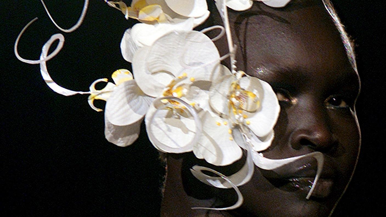 Alek Wek of Sudan wears a hat decorated with flowers.