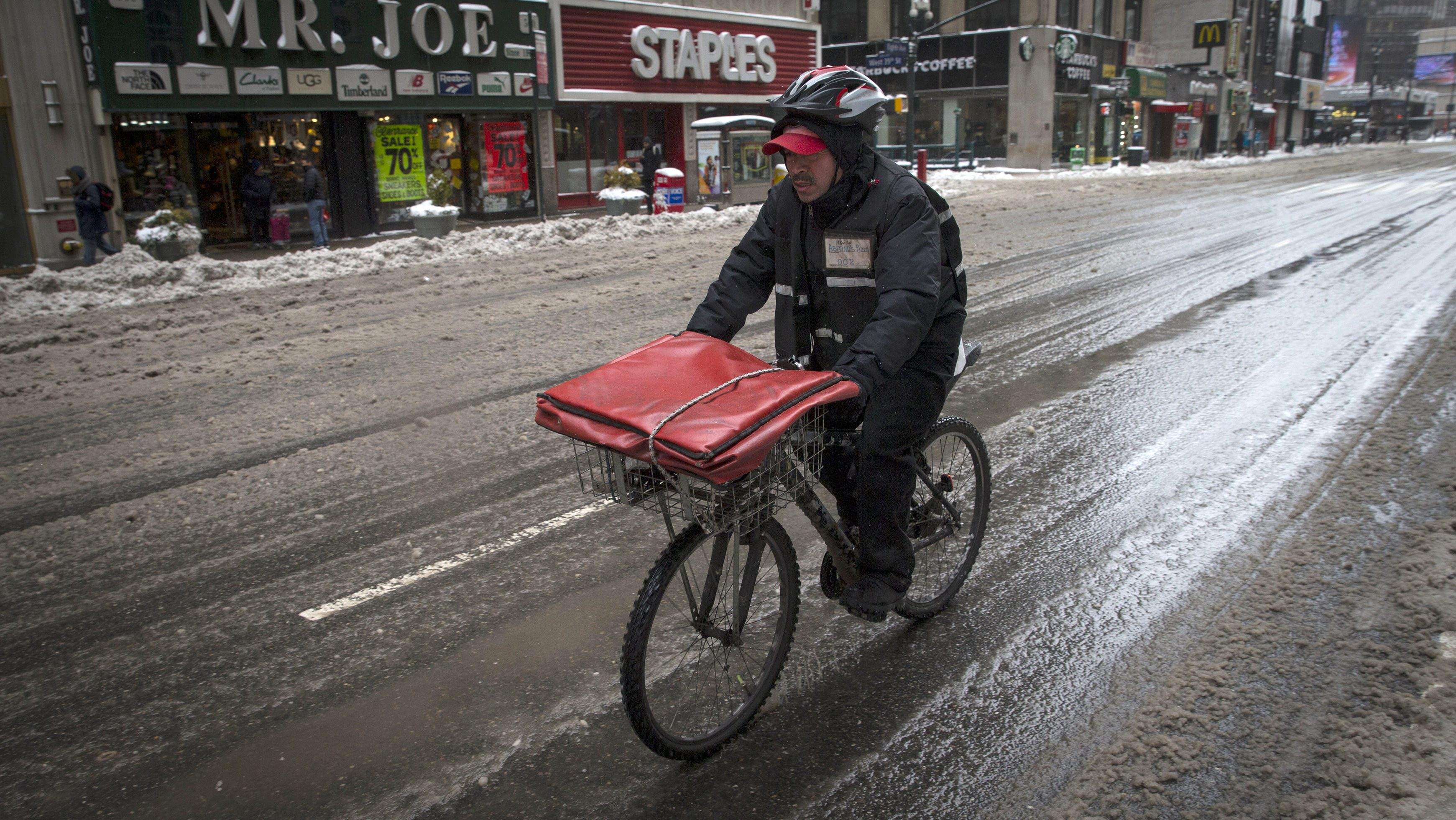 """A pizza delivery man rides on a bicycle on 8th avenue in New York city as the city slowly returned to normal after being hit by winter storm Juno January 27, 2015. A """"life-threatening"""" blizzard barreled into the U.S. Northeast, affecting up to 20 percent of Americans as it kept workers and students housebound, halted thousands of flights and prompted officials to ban cars from roads and shut down public transport.  REUTERS/Mike Segar  (UNITED STATES - Tags: ENVIRONMENT TRANSPORT) - RTR4N6YC"""