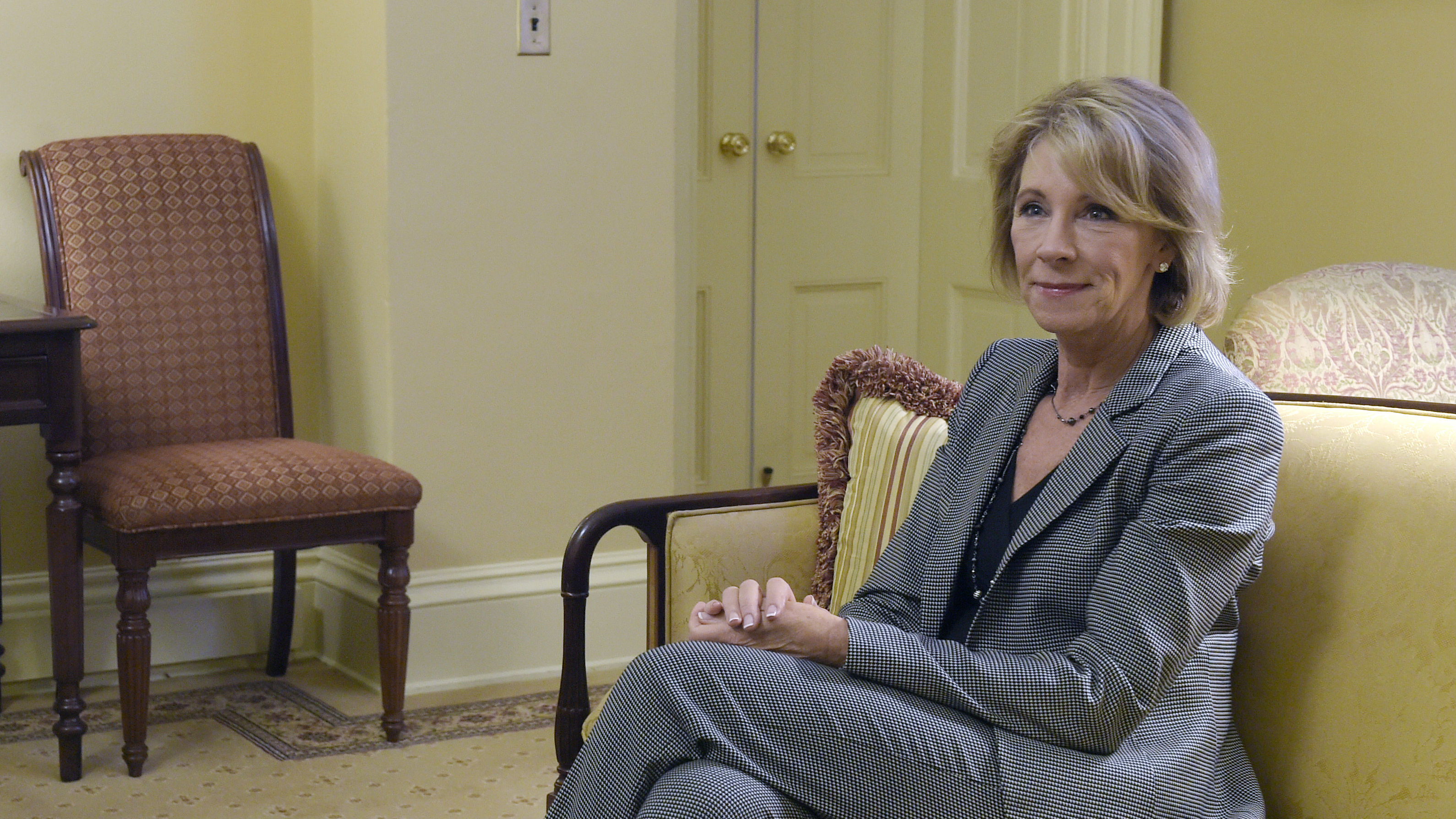 Betsy DeVos sits on a couch.