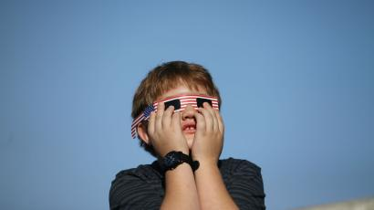 A boy holds his glasses on his face with his fingers during the eclipse.