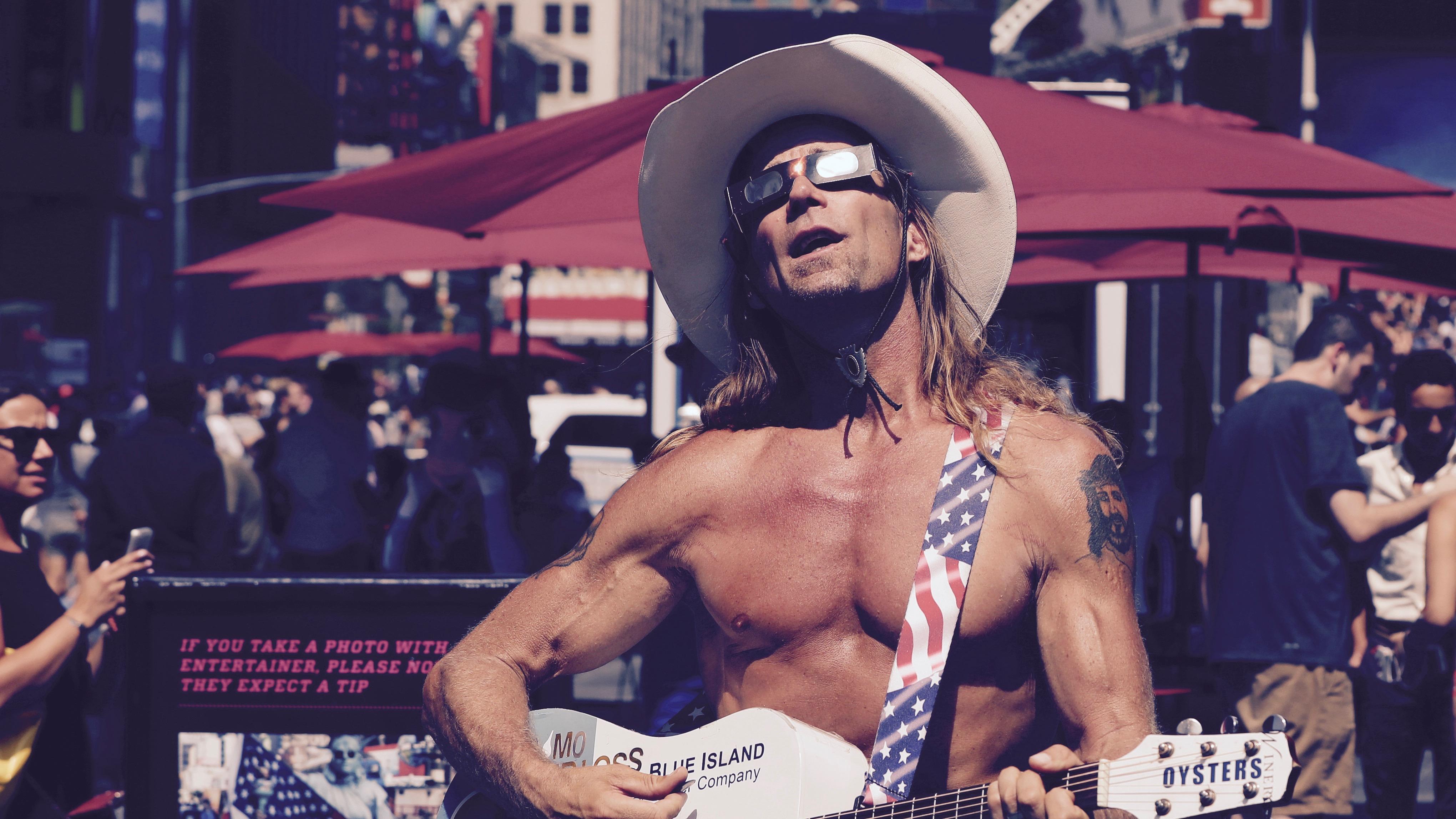 The NY Naked Cowboy plays his guitar while wearing special solar viewers.