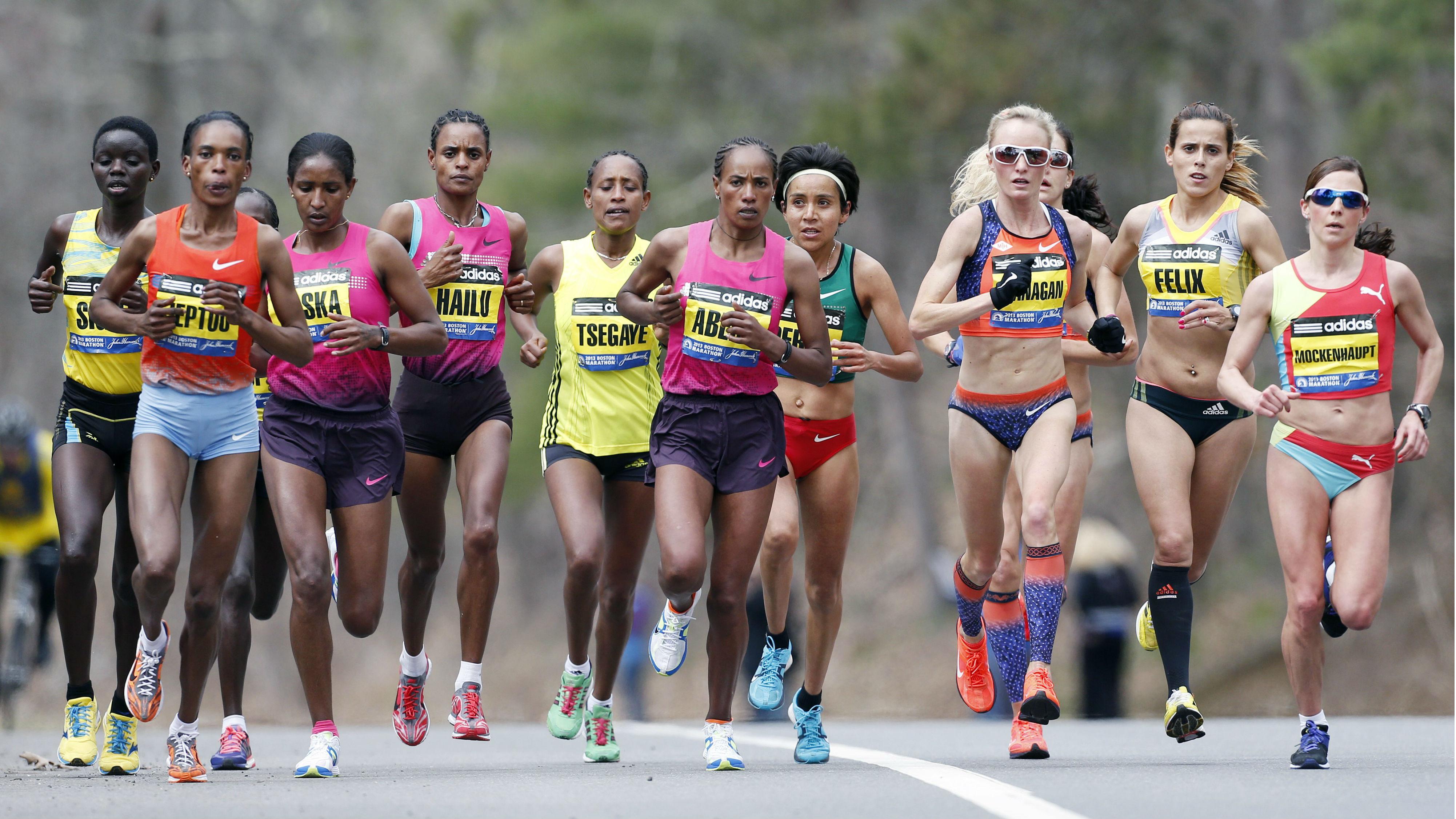 Female marathoners run on a paved road.