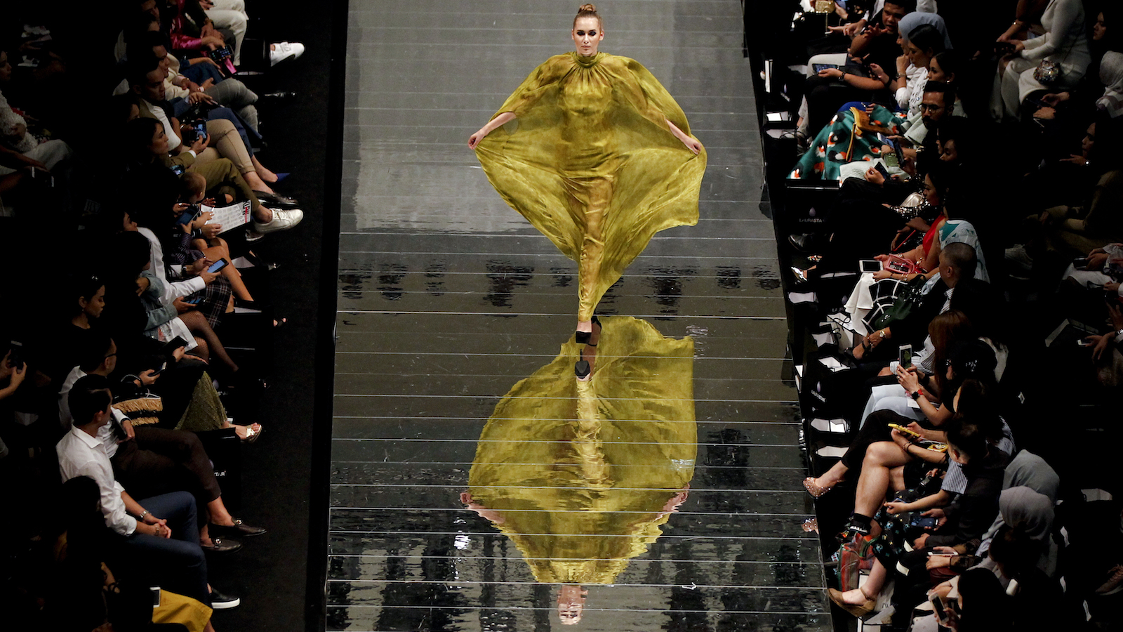 A model wears a creation from  Fiziwoo which reflects on a floor as she walks the runway during the Fashion Week Festival in Kuala Lumpur, Malaysia on Friday, Aug. 18, 2017. (AP Photo/Daniel Chan)
