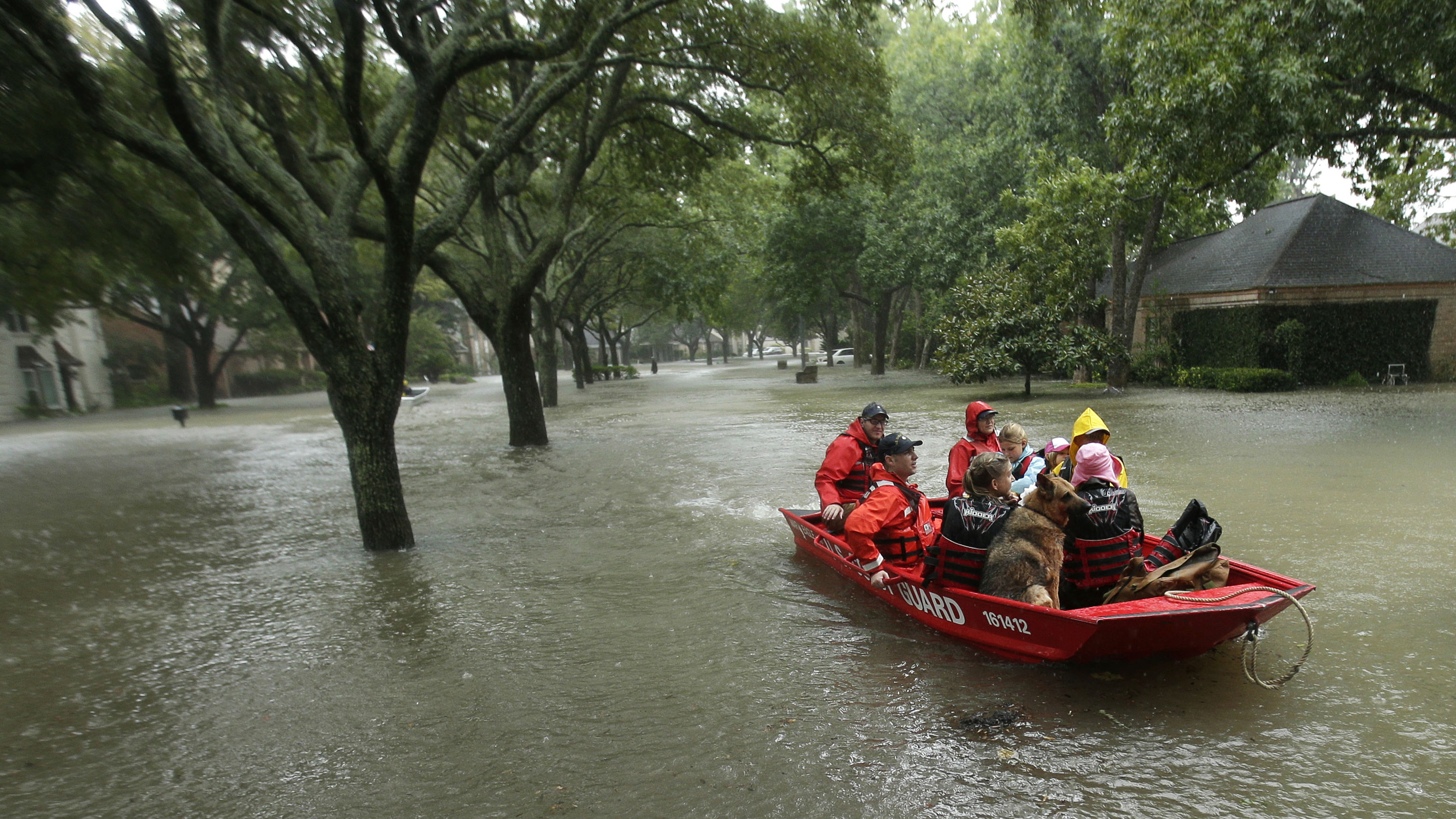 a family floating in a raft with a dog in the floods in Texas.