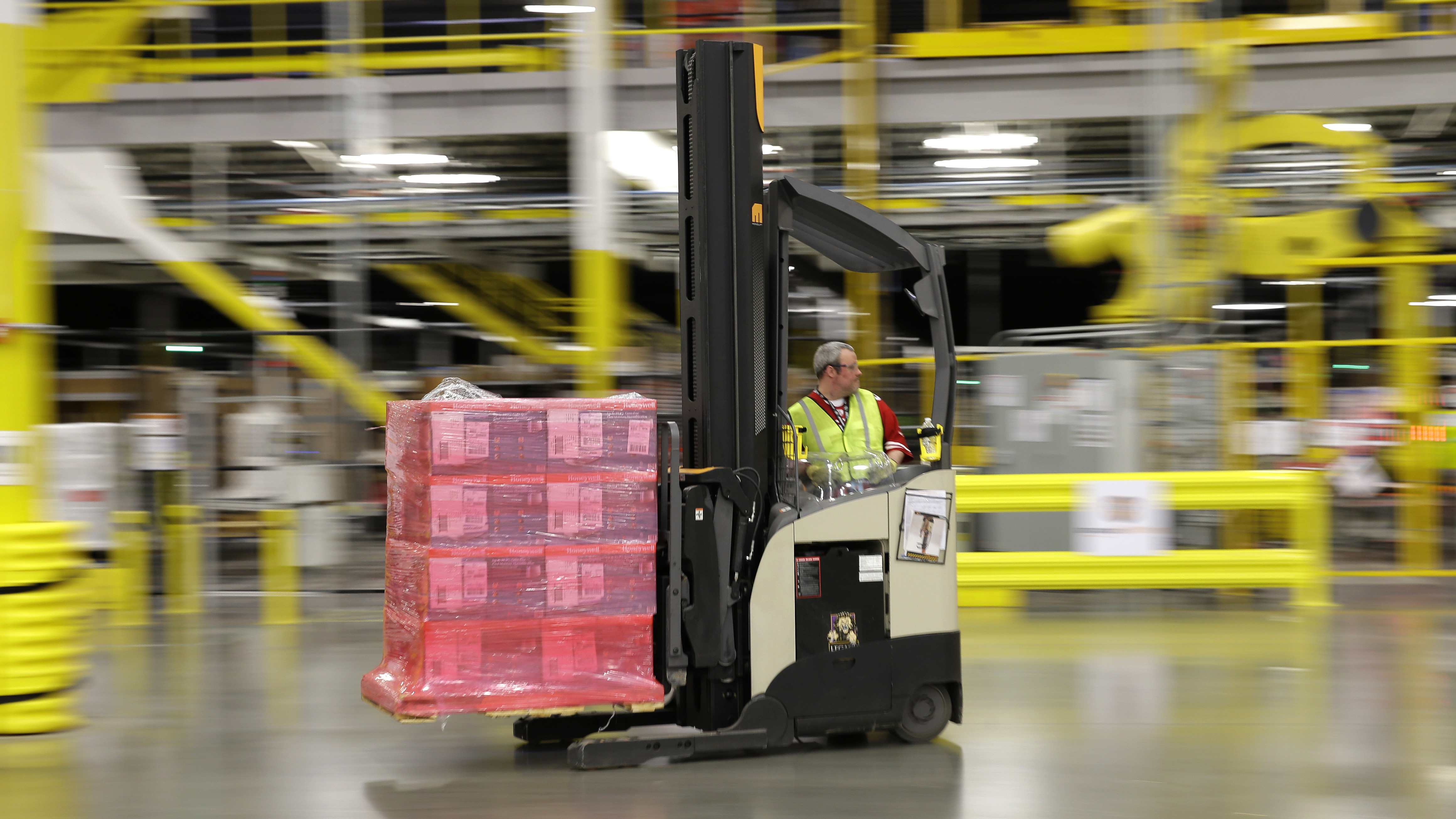 FILE - in this Feb. 13, 2015 file photo, a forklift operator moves a pallet of goods at a Amazon.com fulfillment center in DuPont, Wash. An Illinois corporate tax credit program suspended earlier this summer amid a state budget crisis has since been offered to Amazon because of a previous commitment to the online retailer. Amazon announced its plans in August for a Joliet warehouse that will create 1,000 full-time jobs when it opens. The 500,000-square-foot fulfillment center is its first in Illinois. (AP Photo/Ted S. Warren, File)
