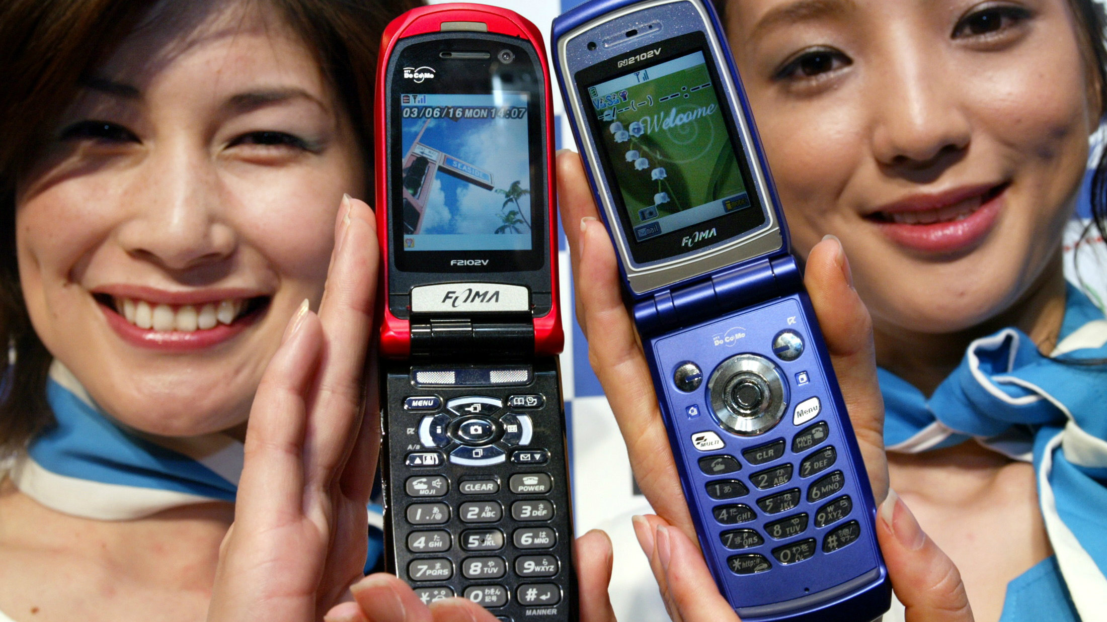 New handsets manufactured by Fujitsu Ltd (L) and NEC Corp are displayed at an unveiling in Tokyo June 16, 2003. Japan's NTT DoCoMo Inc said on Monday it would offer the two handsets with longer battery life for its third-generation (3G) service in the next few months in a bid to spur demand for the fledgling service.