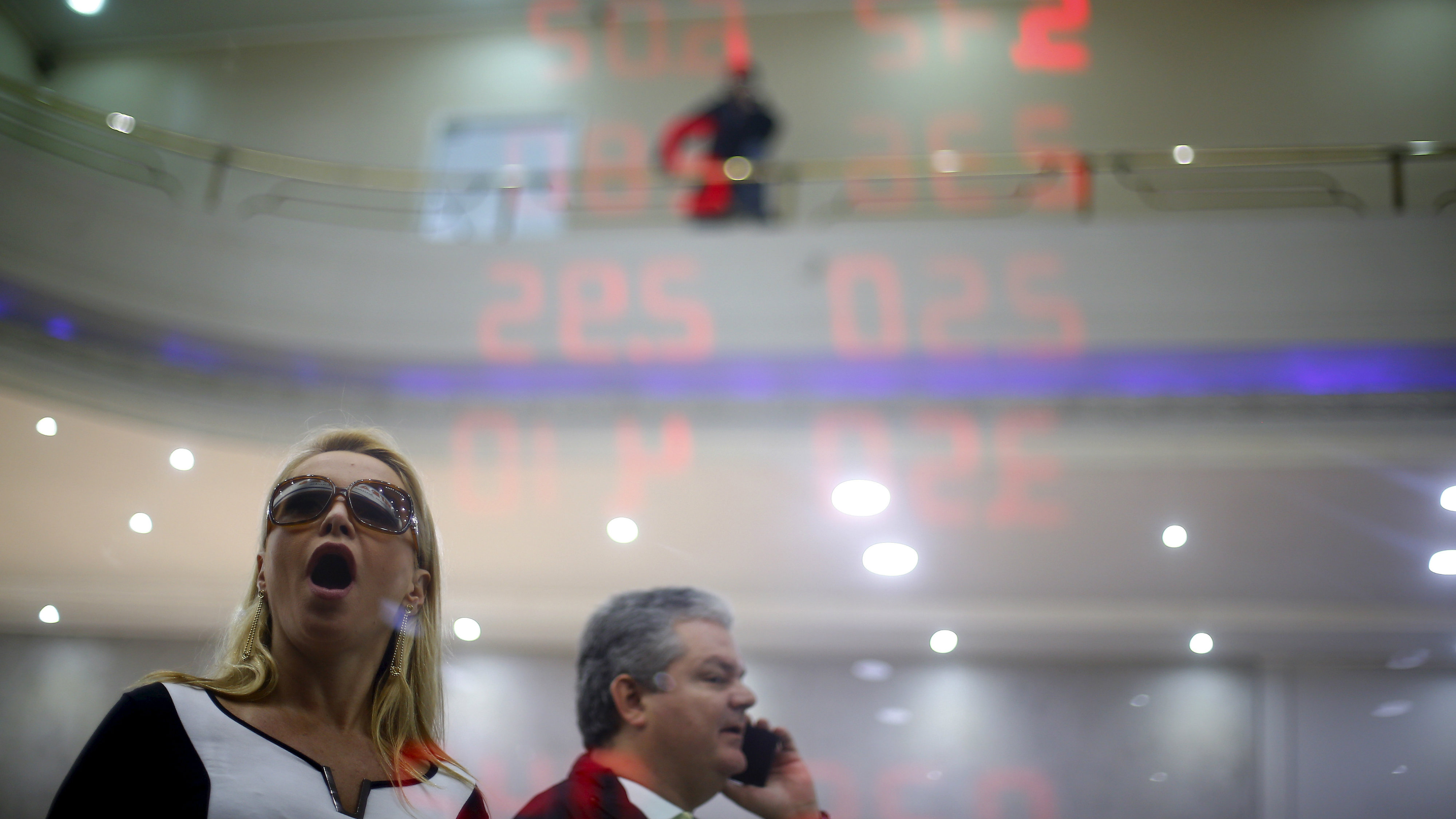 A woman reacts as she reads a board showing the Real-U.S. dollar and several foreign currencies exchange rates in Rio de Janeiro, Brazil, August 26, 2015. While many of Brazil's largest companies have grown savvy about hedging their debt against big currency swings, an increasing number could feel the heat from the real's plunge to a more than 12-year low due to poor planning and rising debt, bankers said. Debt refinancing and hedging costs are rapidly rising as Brazil's economy falls into recession and local banks pare back credit. The real, the world's worst-performing major currency this year, according to Thomson Reuters calculations, slipped below 3.65 to the dollar on Wednesday.