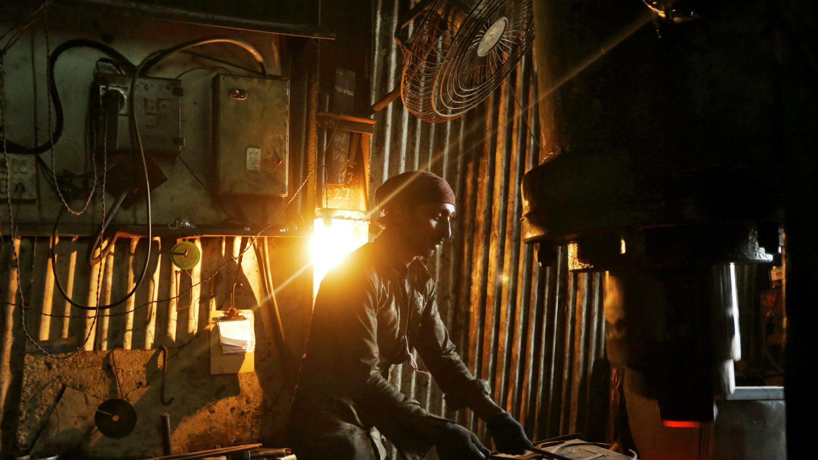 A worker operates a hydraulic press machine at a workshop manufacturing flanges for automobiles in Mumbai...